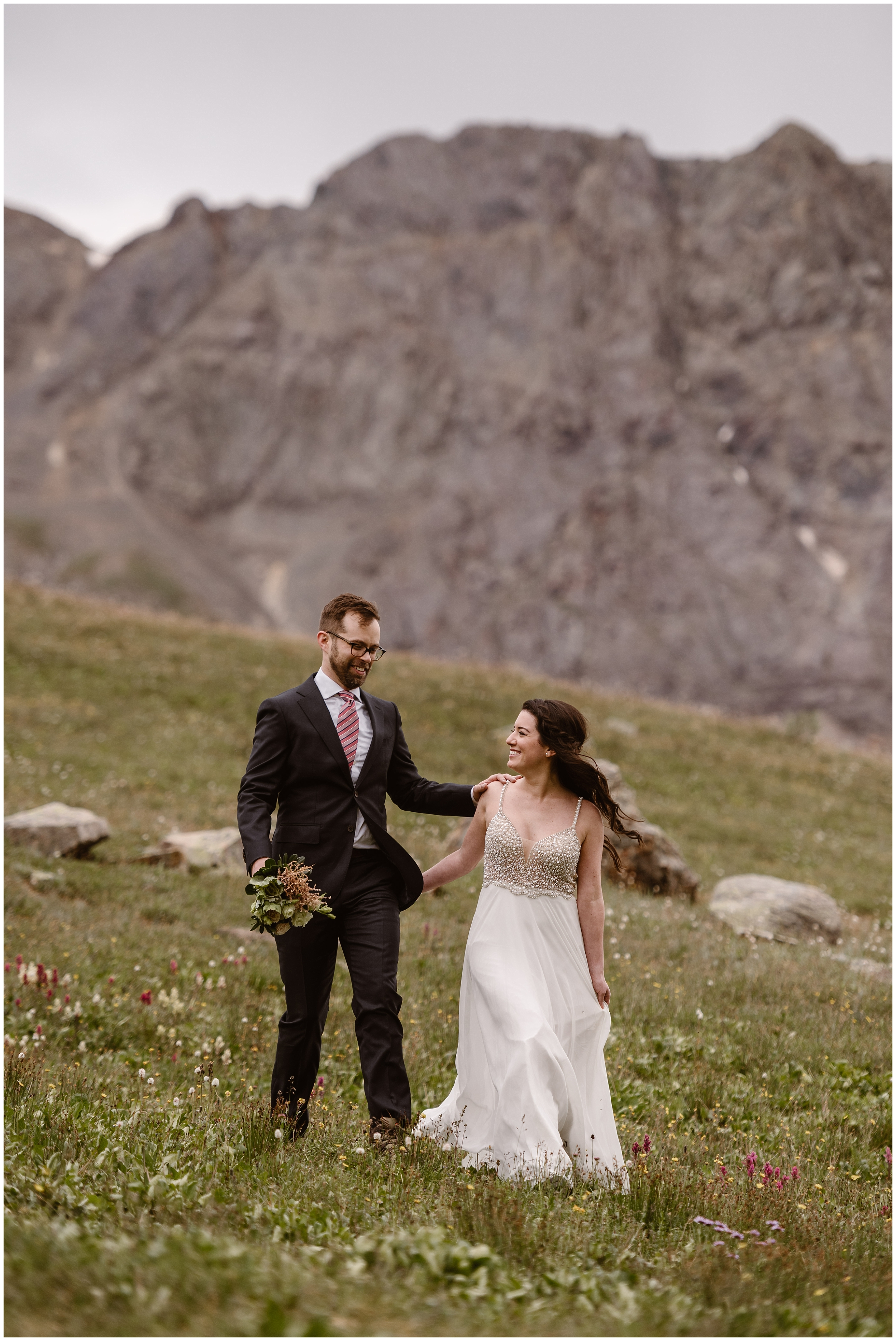 Logan, the groom, puts his arm on Katie's shoulder as he follows close behind her in a green, mountainside meadow. In his other hand, he holds Katie's bouquet of flowers. In these adventure elopement pictures, Katie looks back at Logan with a giant smile on her face as they head to their destinatino for their adventure elopement.