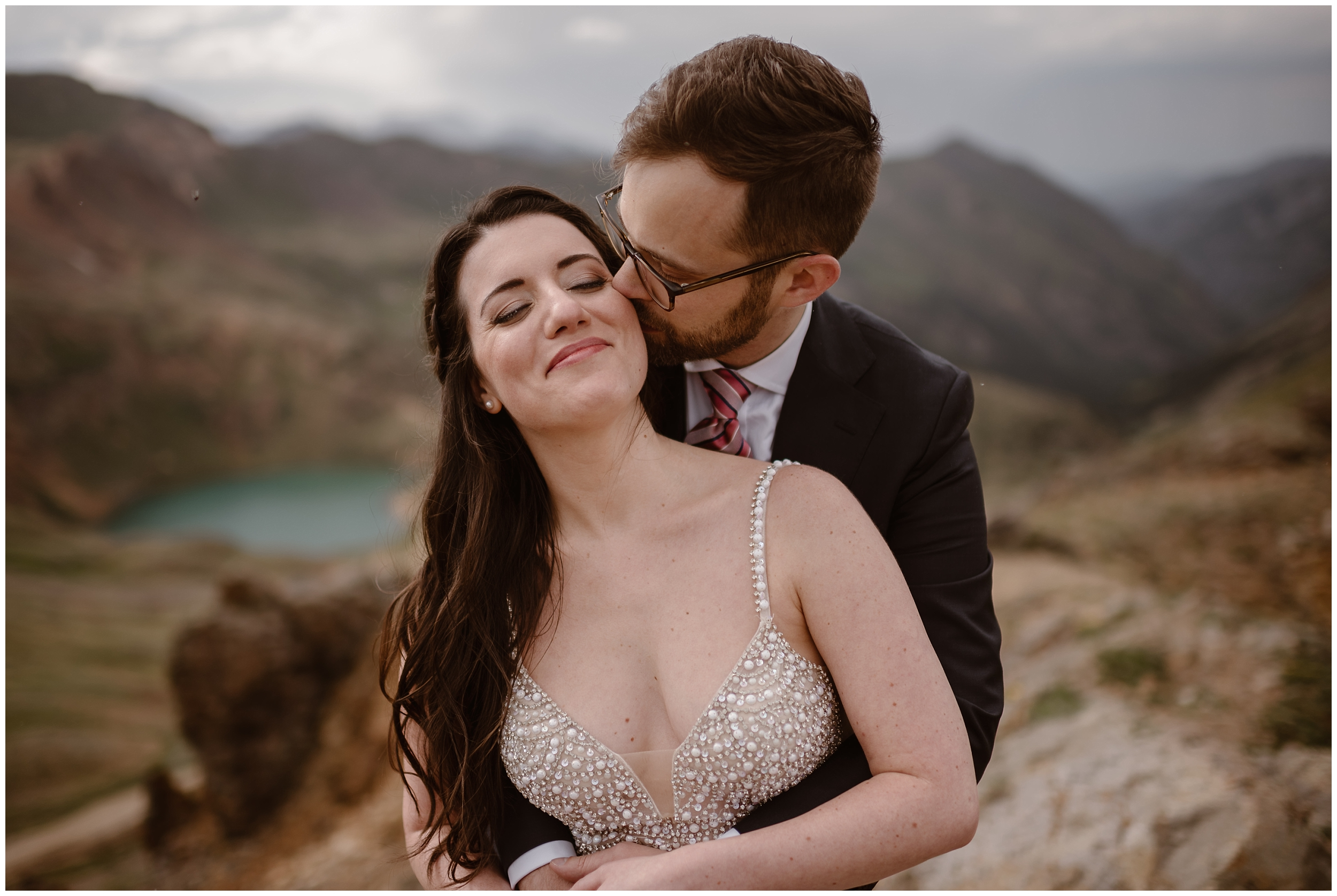 Logan, the groom, holds his bride, Katie by wrapping his arms around her. Katie, shown from the bodice of her pearl wedding dress up, shuts her eyes and leans into her groom's kiss, smiling an enormous smile. The two stand at the forefront of the image, but in the background, a striking, turquoise alpine lake can be seen in the distance at the bottom of the basin.