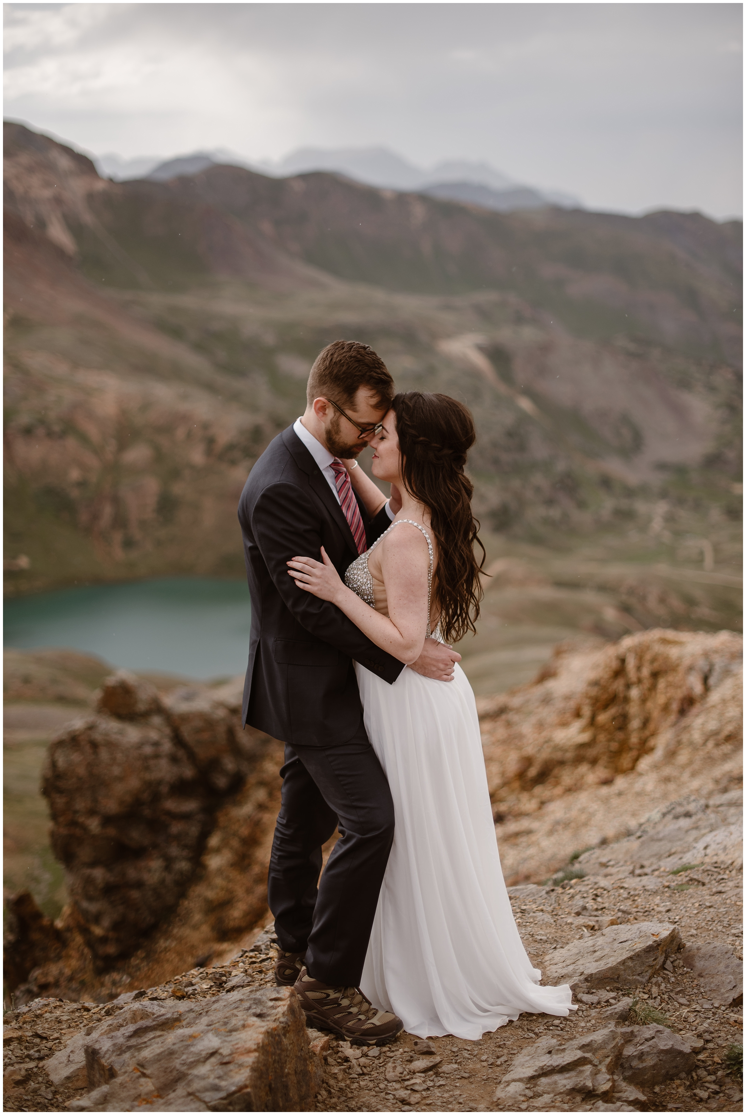 Katie and Logan, the bride and groom, embrace and hold their foreheads close together at the top of a rocky mountainside. Below them, a turquoise alpine lake is shown at the bottom of the basin. This location was one of the best elopement ideas that Katie and Logan wanted for their Colorado mountain wedding.