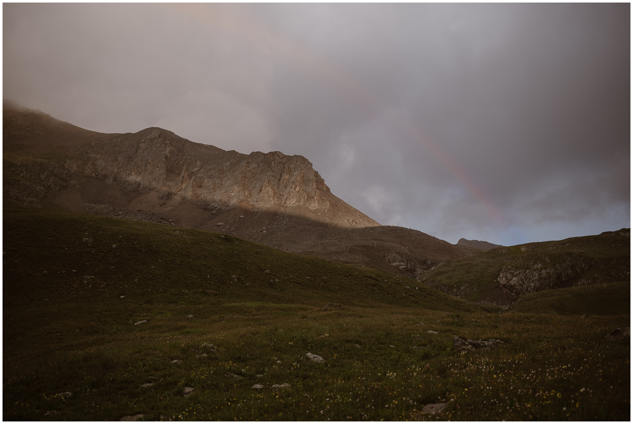 A rainbow crests over the top of a granite mountain, a shadow cast on the bottom by the green meadow beneath it. Katie and Logan, the bride and groom, waited in the adventure Jeep while the sudden storm passed. As soon as it was over, they climbed out to continue their elopement ceremony.