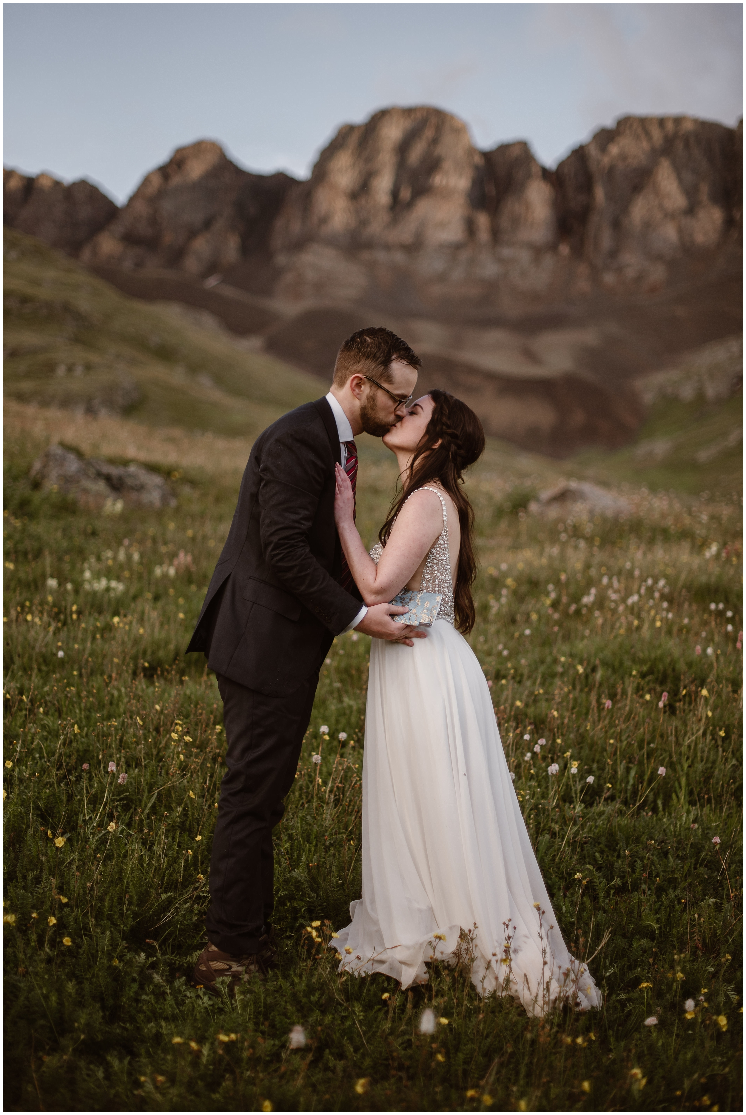 Katie and Logan, the bride and groom, lean in close to kiss at the close of their secluded elopement ceremony. The two of them stand in a wildflower-covered meadow at the basin of a Colorado mountain. Their Colorado mountain wedding was chosen by them because they wanted a location that required off road driving and an adventure Jeep.