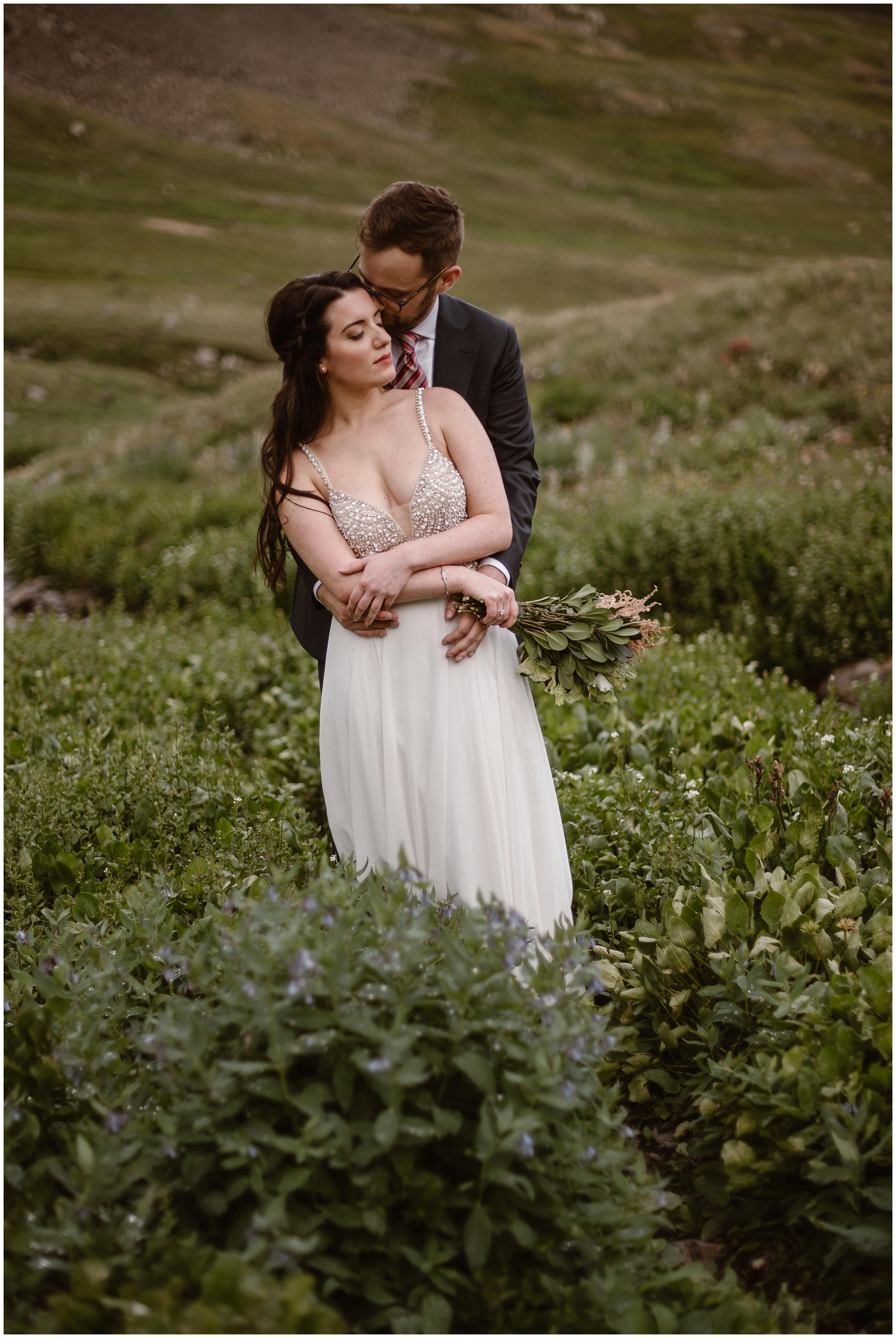 The bride and groom, Katie and Logan, stand in a green meadow surrounded by wildflowers after their elopement ceremony. Small simple wedding ideas like Kaite and Logan's typically involve couples traveling to spots for destination elopements. In Katie and Logan's case, they chose a location that required an adventure Jeep for off road driving to their secluded spot.