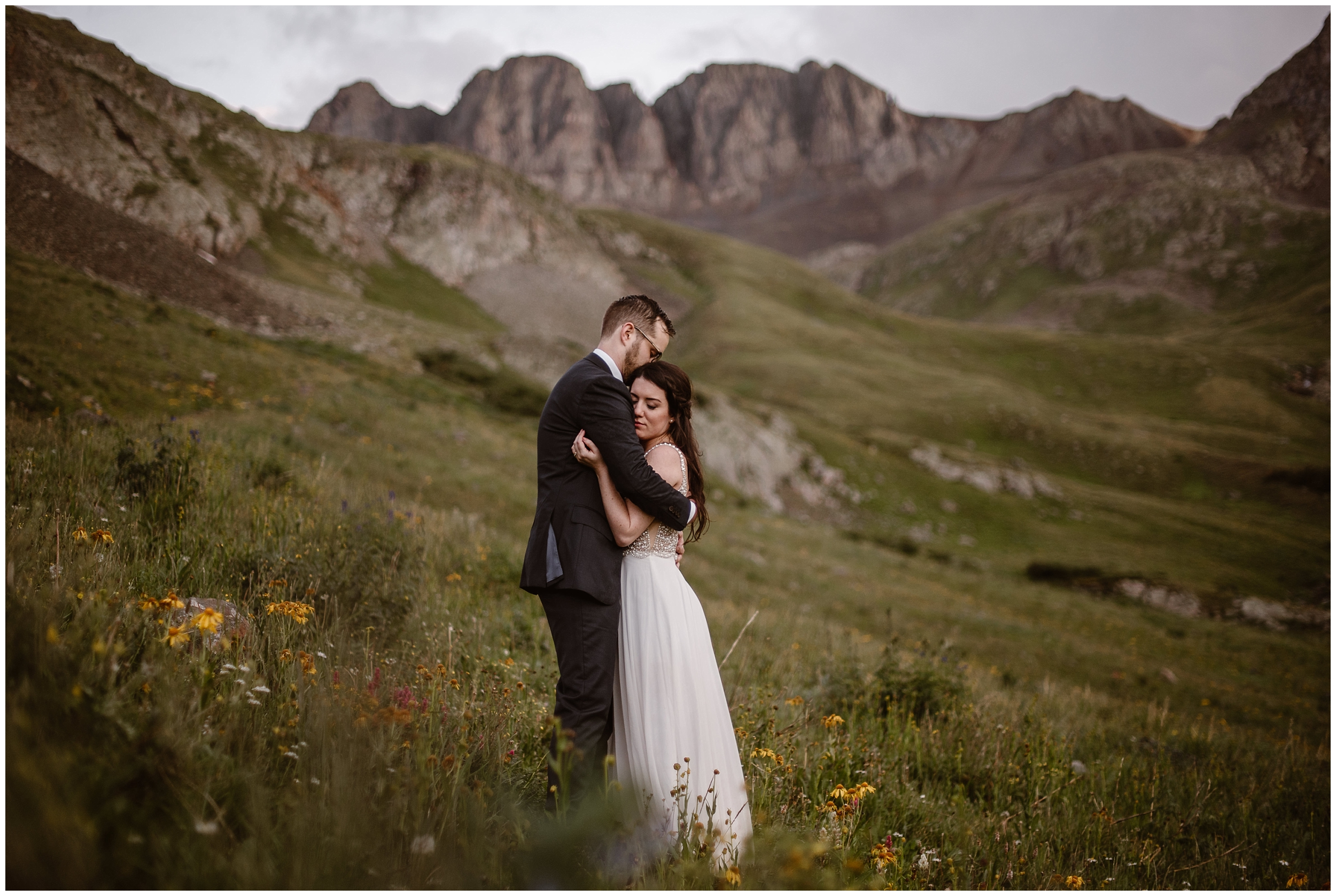 The bride and groom meaningfully embrace in a meadow in a mountain basin. All around them wildflowers in red and yellow bloom by their feet in these elopement pictures captured by adventure photographers Adventure Instead. Katie and Logan's small simple wedding was held in Ouray, Colorado.