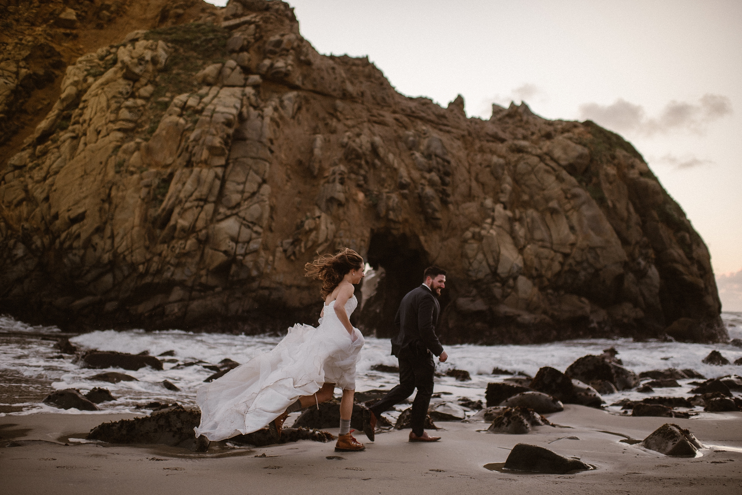 A bride and groom run along the rocky, sandy beach of the Oregon Coast. The bride, pulling her dress up to reveal hiking boots beneath chases after her groom as they head toward the water, an enormous boulder looming in the background. These adventure elopement pictures were captured by Adventure Instead, an Oregon elopement photographer.