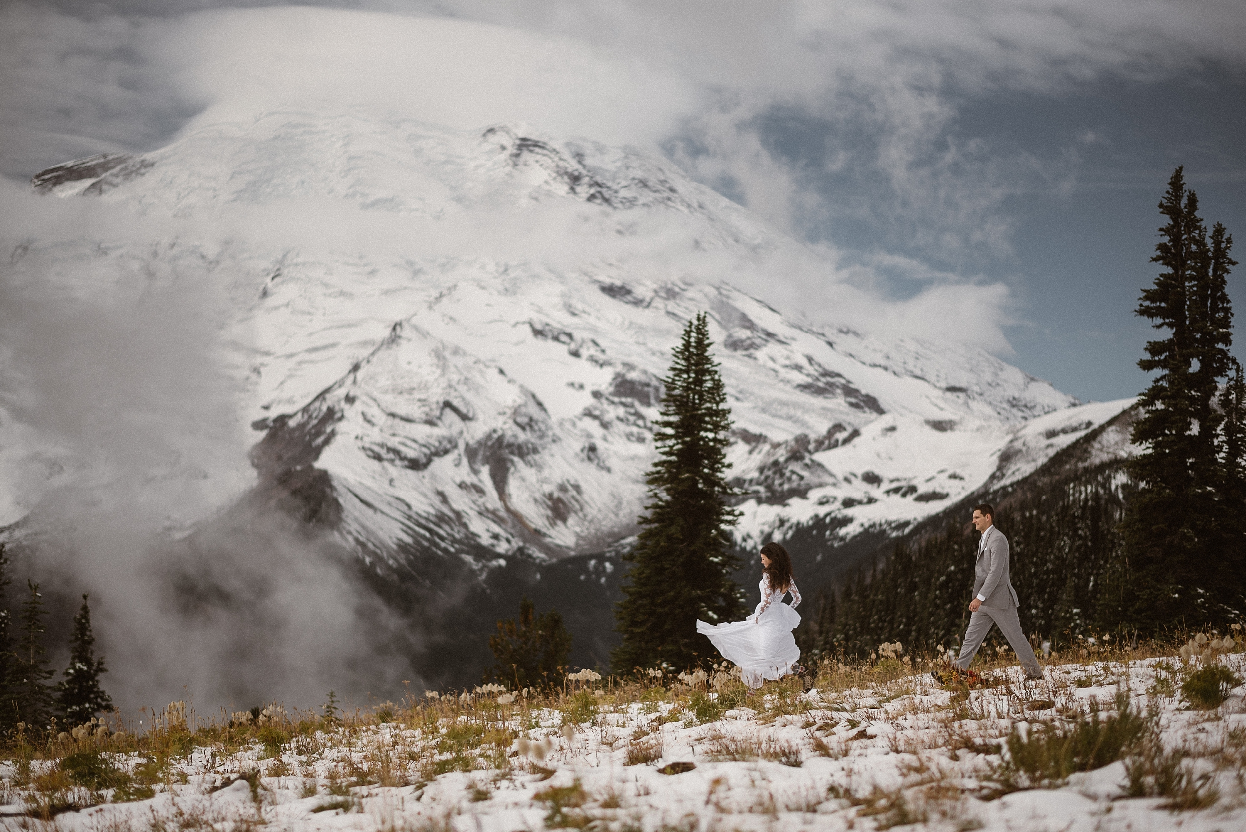 A bride and groom run through a snow-covered meadow. Tall evergreen trees poke up behind them. In the distance, a snowy, granite covered mountain looms. The groom walks behind his bride, who is running and holding up the skirt of her wedding dress. These elopement photos were captured by Adventure Instead, a Washington elopement photographer.