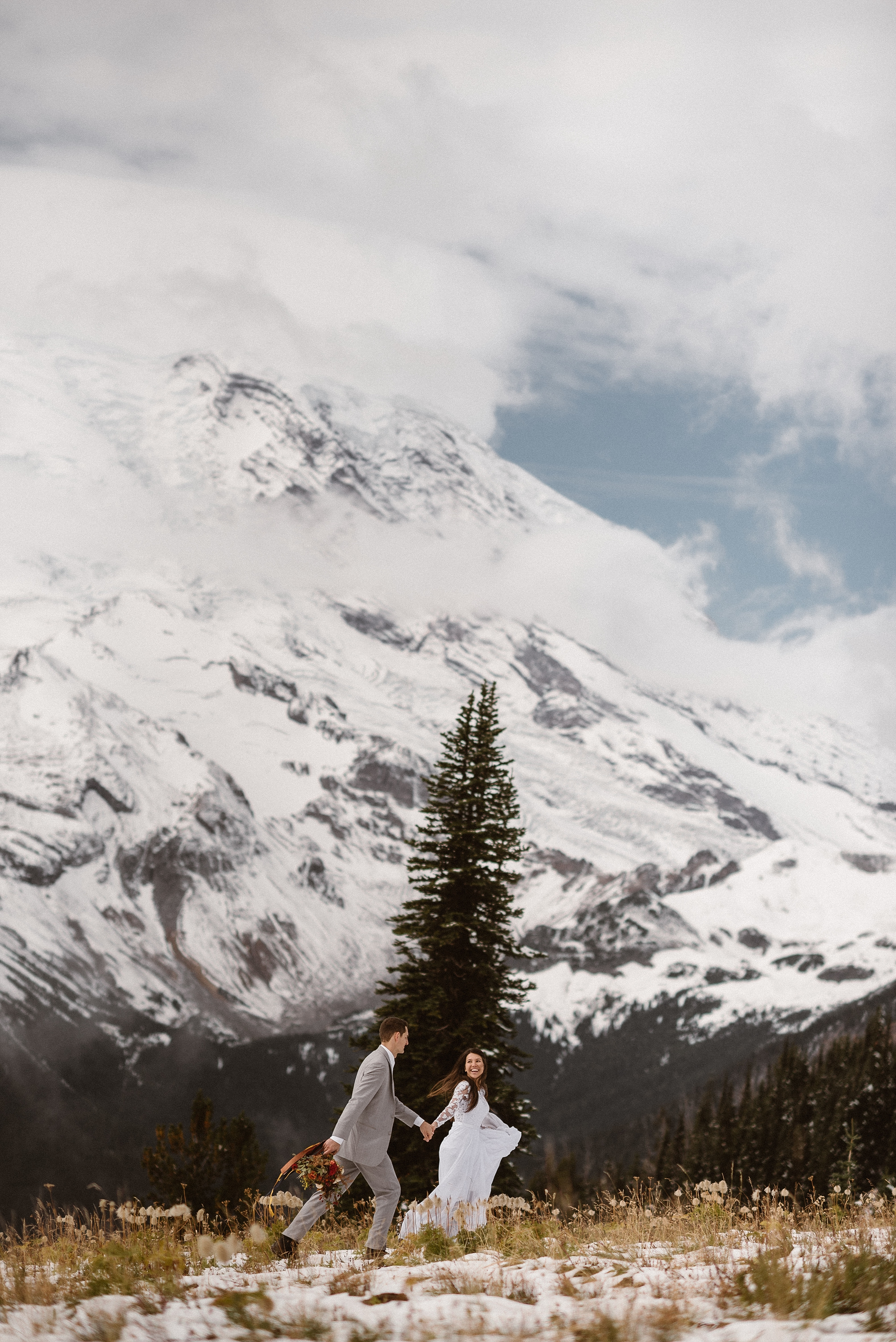 Mount Rainier stands in the background, vast amounts of ice and snow covering the granite mountain. A bride and groom, closer to the camera, hold hands and run through a snow-covered meadow that has tufts of grass and wildflowers peeking through. At the center of the image is a tall, dark-green fir tree.