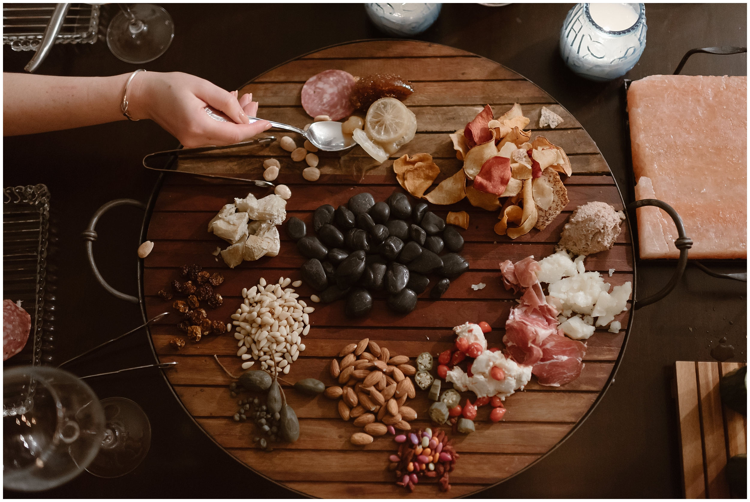 An enormous, circular wooden charcuterie board is on the table of an Ouray, Colorado Airbnb that the bride and groom are staying at. Almonds, meats, cheeses, and other gourmet items are strewn about the wooden board.These delicious food were courtesy of a professional chef the two hired as part of their reception after eloping.
