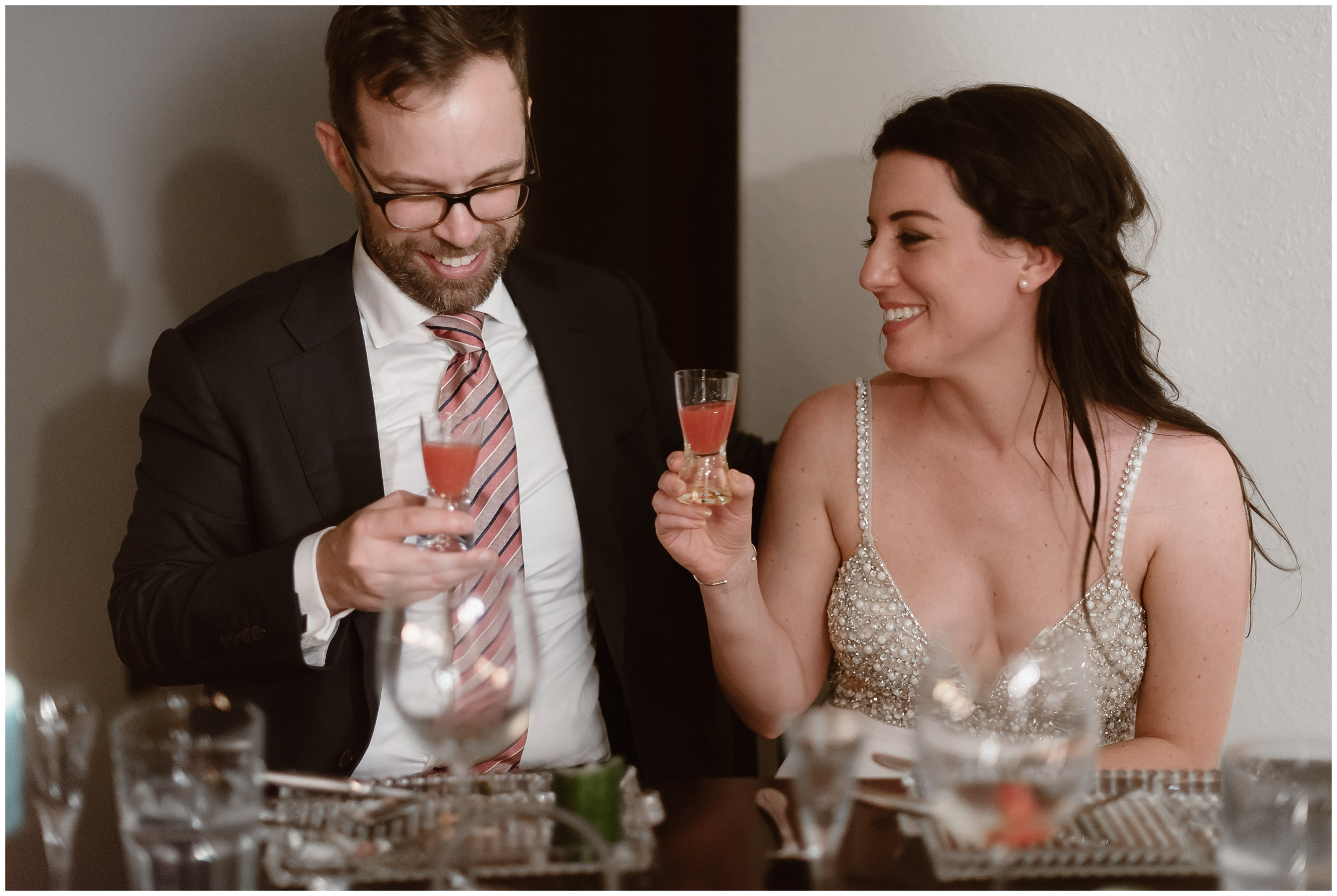 Katie and Logan sit at a table filled with gourmet food and drink prepared by their hired private chef. Katie looks at Logan, who's looking down at his glass of orange-pink beverage. They're about to cheers their Colorado mountain wedding.