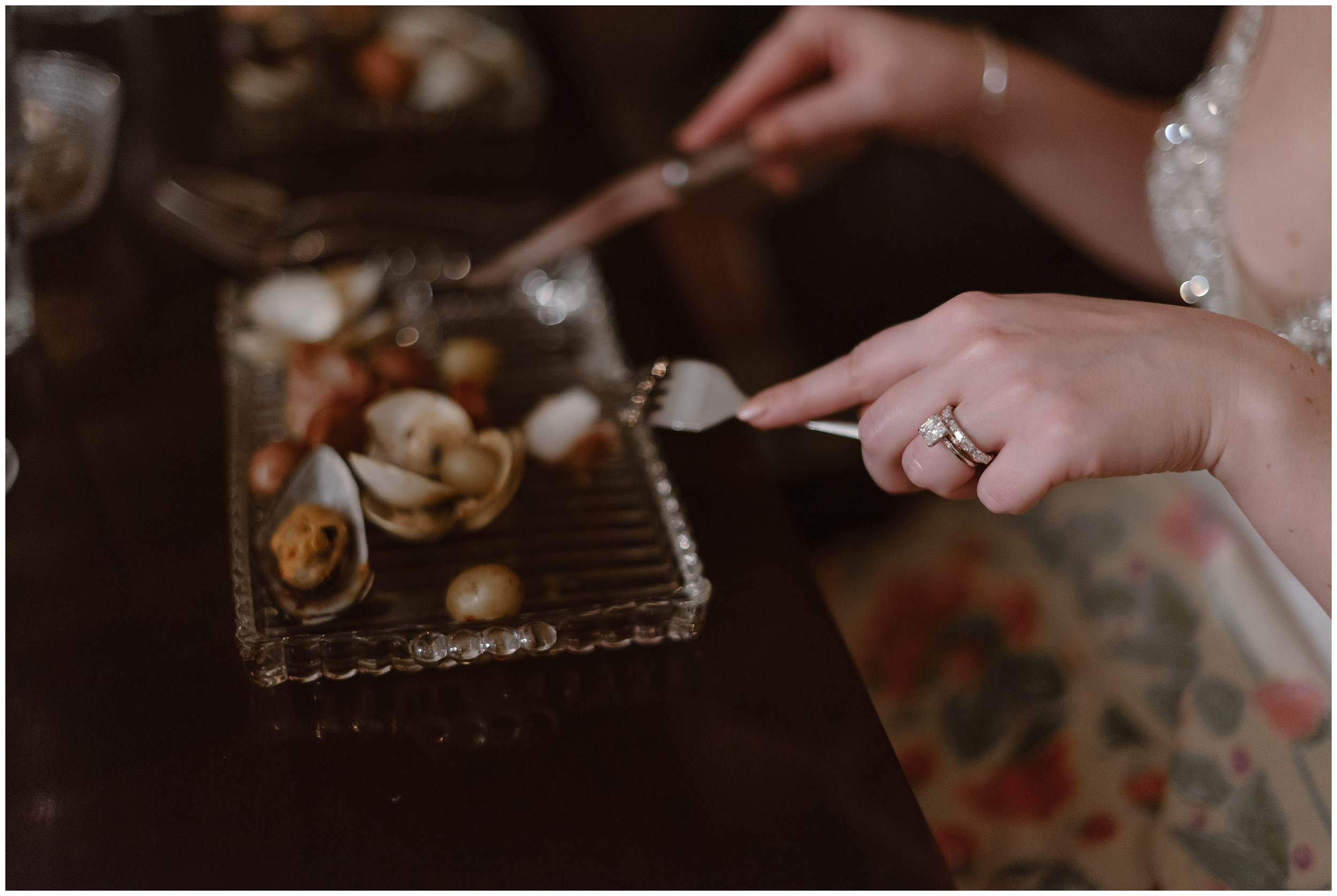 The bride uses her knife and fork to cut into a beautiful selection of gourmet food prepared by the private chefs she and her new husband hired as part of their reception after eloping.