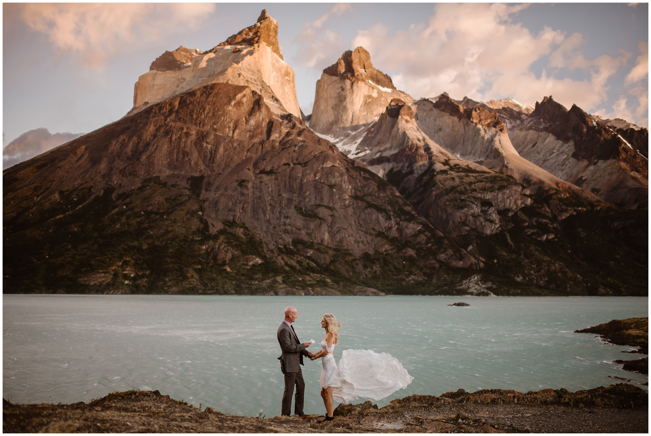 A bride and groom stand in front of a turquoise alpine lake with jagged, dramatic mountains in the background. The couple is having their wedding ceremony in this adventurous location. The brides dress flies up in the wind as her groom read his vows to her. These elopement pictures were captured by Adventure Instead, an elopement wedding photographer.