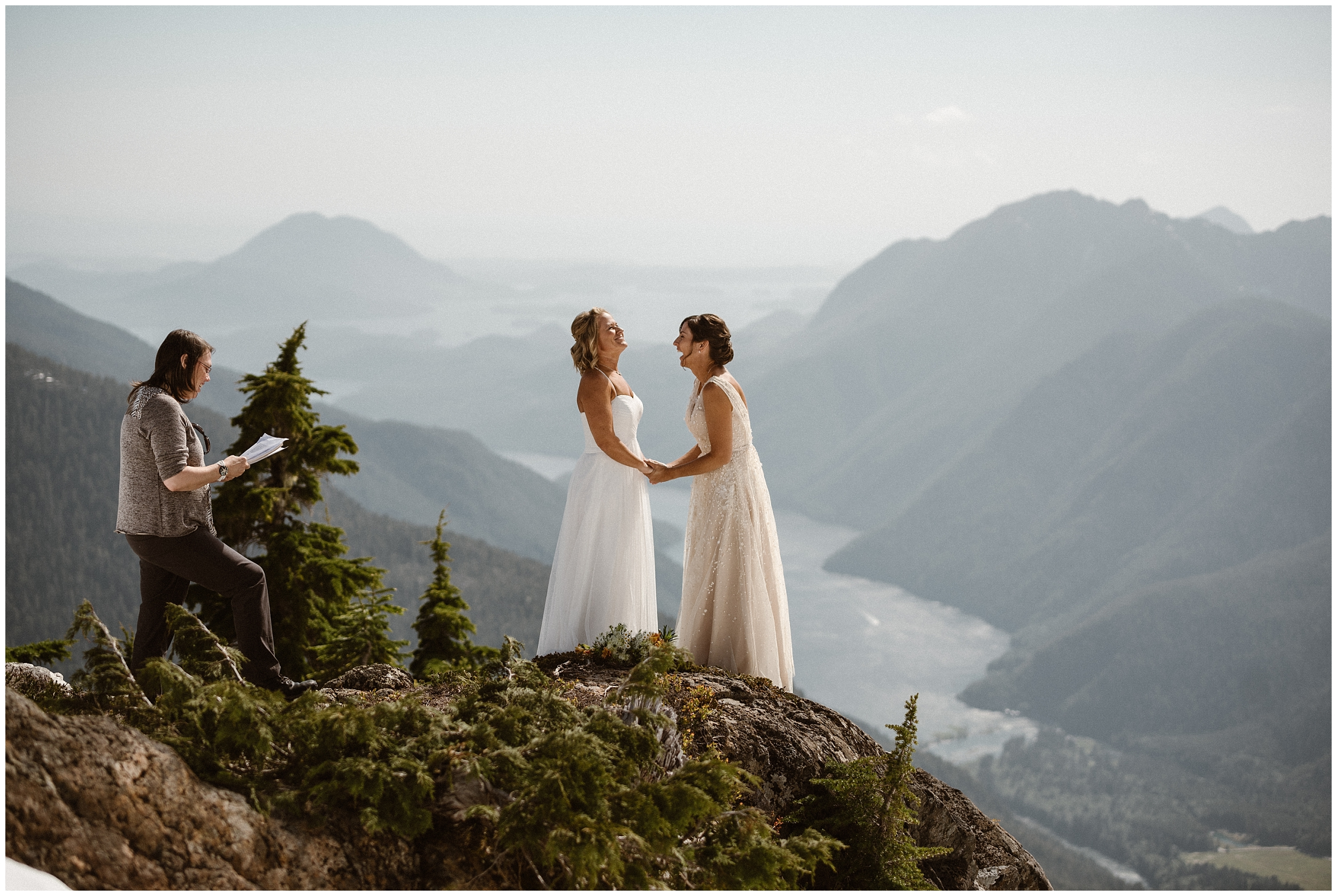 Two brides take hands a top a mountain peak, laughing as they run through their wedding ceremony outline. An officiant reads their unique wedding ceremony script on the mountain peak as well. In the background of these elopement pictures, more mountain ranges, lush foliage, and a river can be seen.