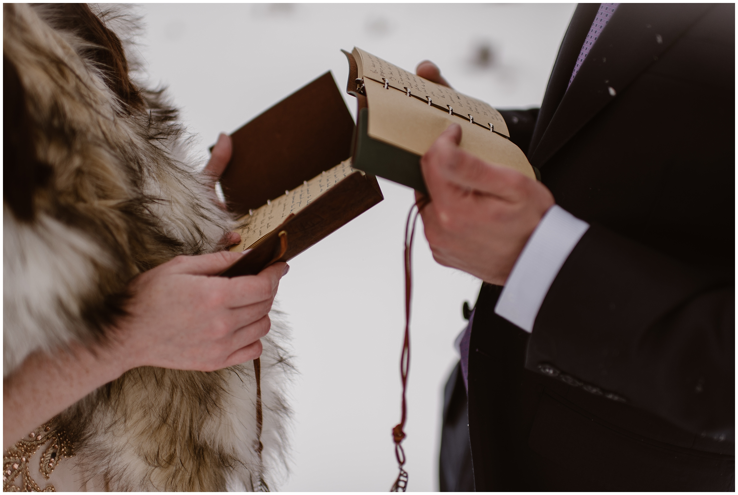 A bride and groom hold their leather, vow books as they read their vows during their marriage ceremony. This image, captured by Adventure Instead, a photographer who specializes in small wedding photos, shows a closeup on the bride and grooms hands as they read through their handwritten vows.