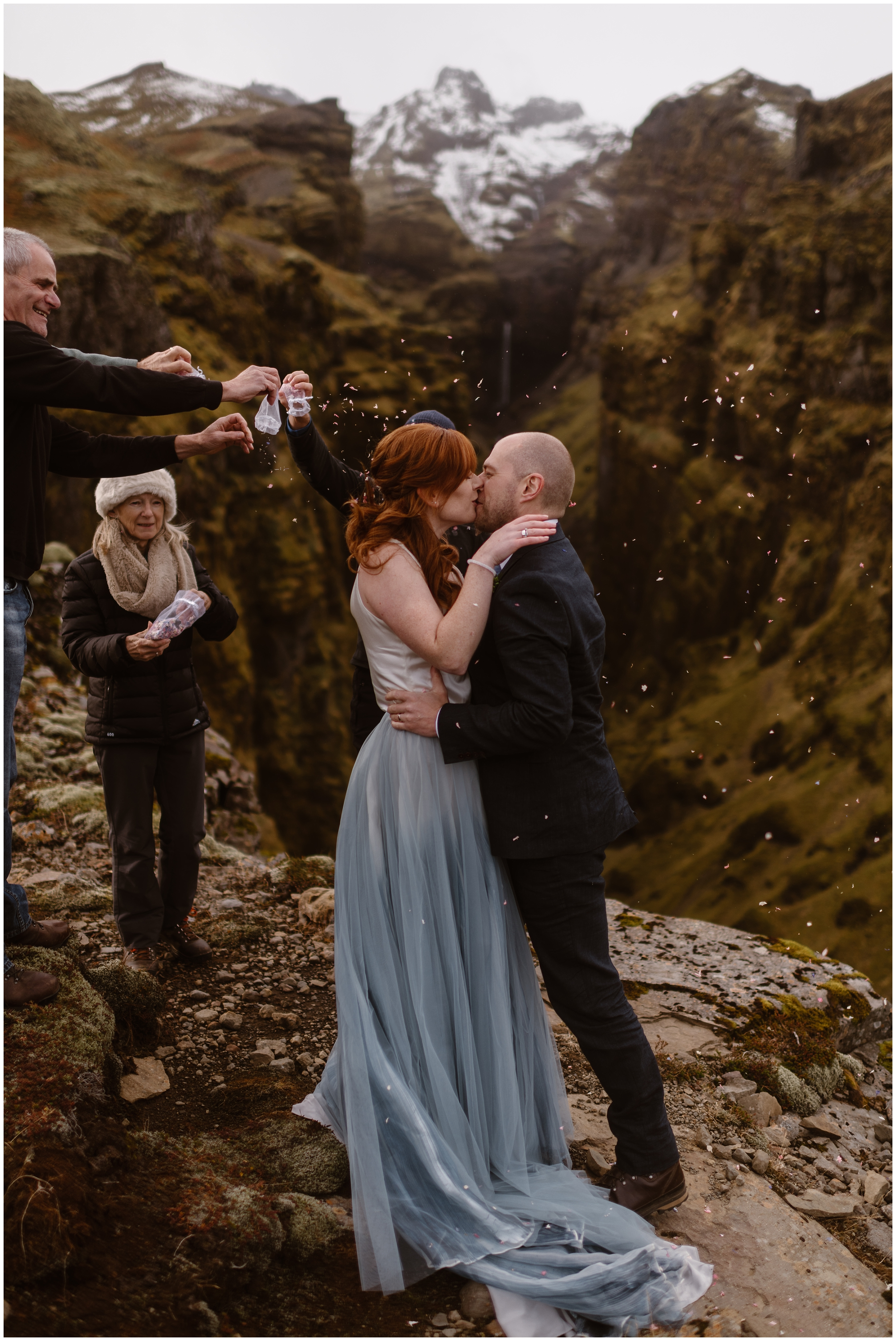 A bride and groom kiss as they stand on top of a lush, green mountainside. The bride, in a striking light blue gown, leans into her new husband as friends and family members empty flower petals from small bags all around them.