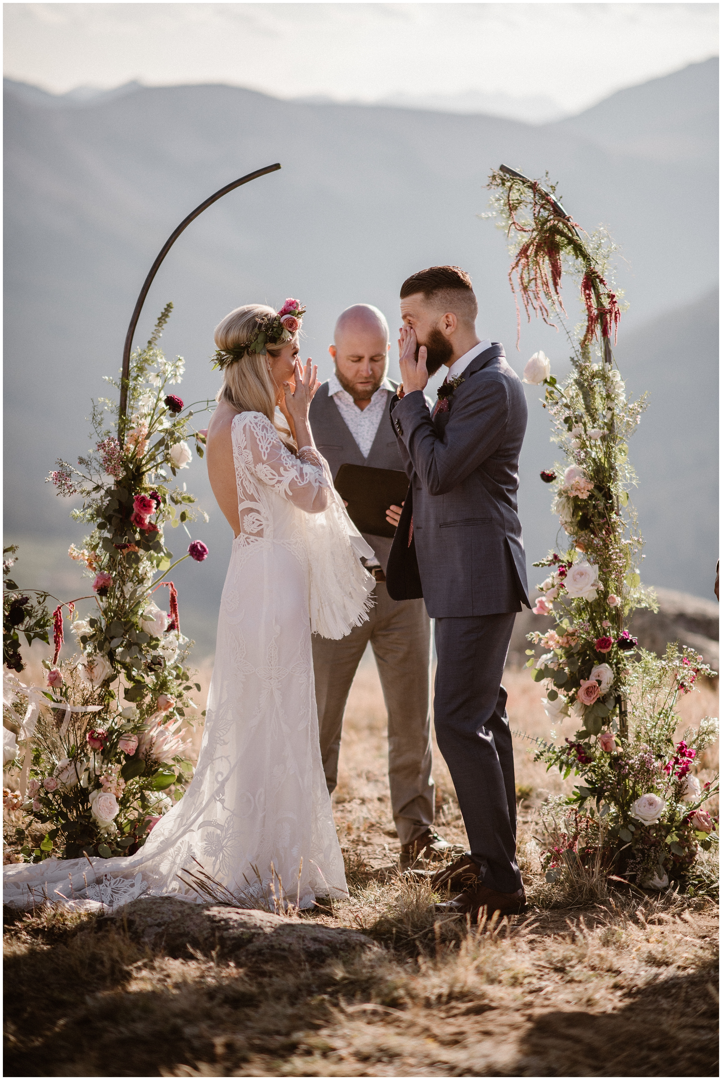 A bride and a groom both stand in front of a gorgeous, flowered arch as their officiant reads through their wedding ceremony outline. Both the bride and groom wipe tears away from their eyes.