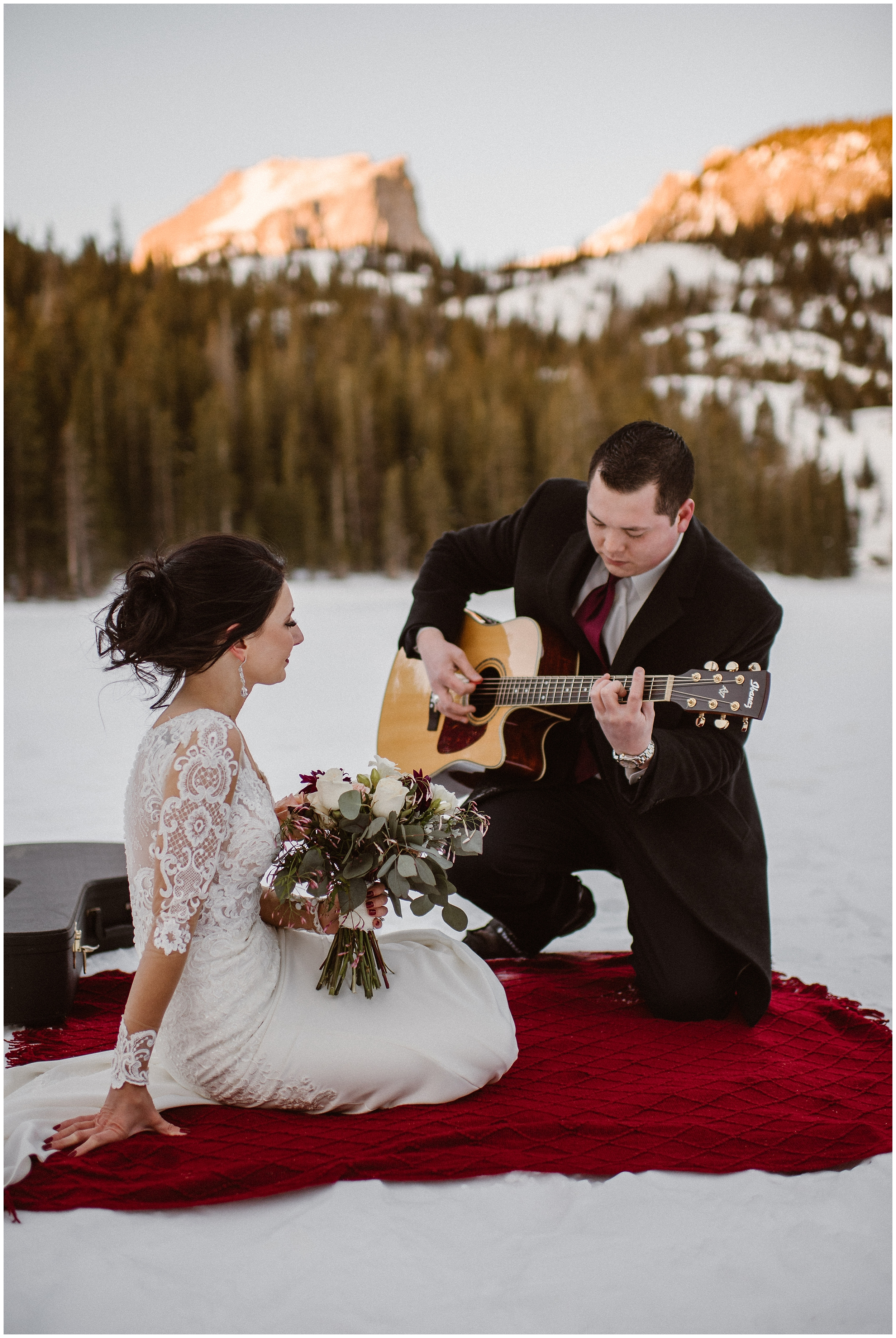 A groom plays the guitar for his bride as he kneels on a bright red blanket. The bride, sitting on the blanket with the groom, holds a beautiful bouquet of flowers. All around them a snowy paradise can be seen. This elopement photo was captured by Adventure Instead, an elopement wedding photographer.