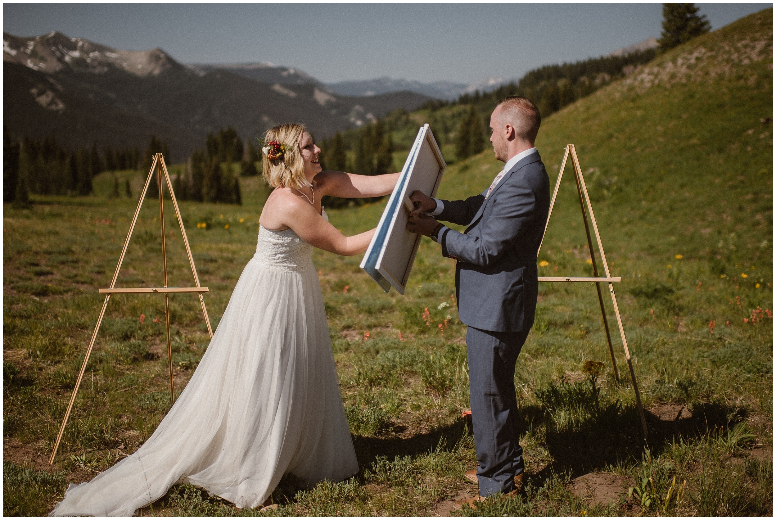 A couple rubs together two easels on their wedding day as a part of their non-traditional wedding ceremony. This commitment ceremony symbolizes how the two of them are becoming one on their elopement day.