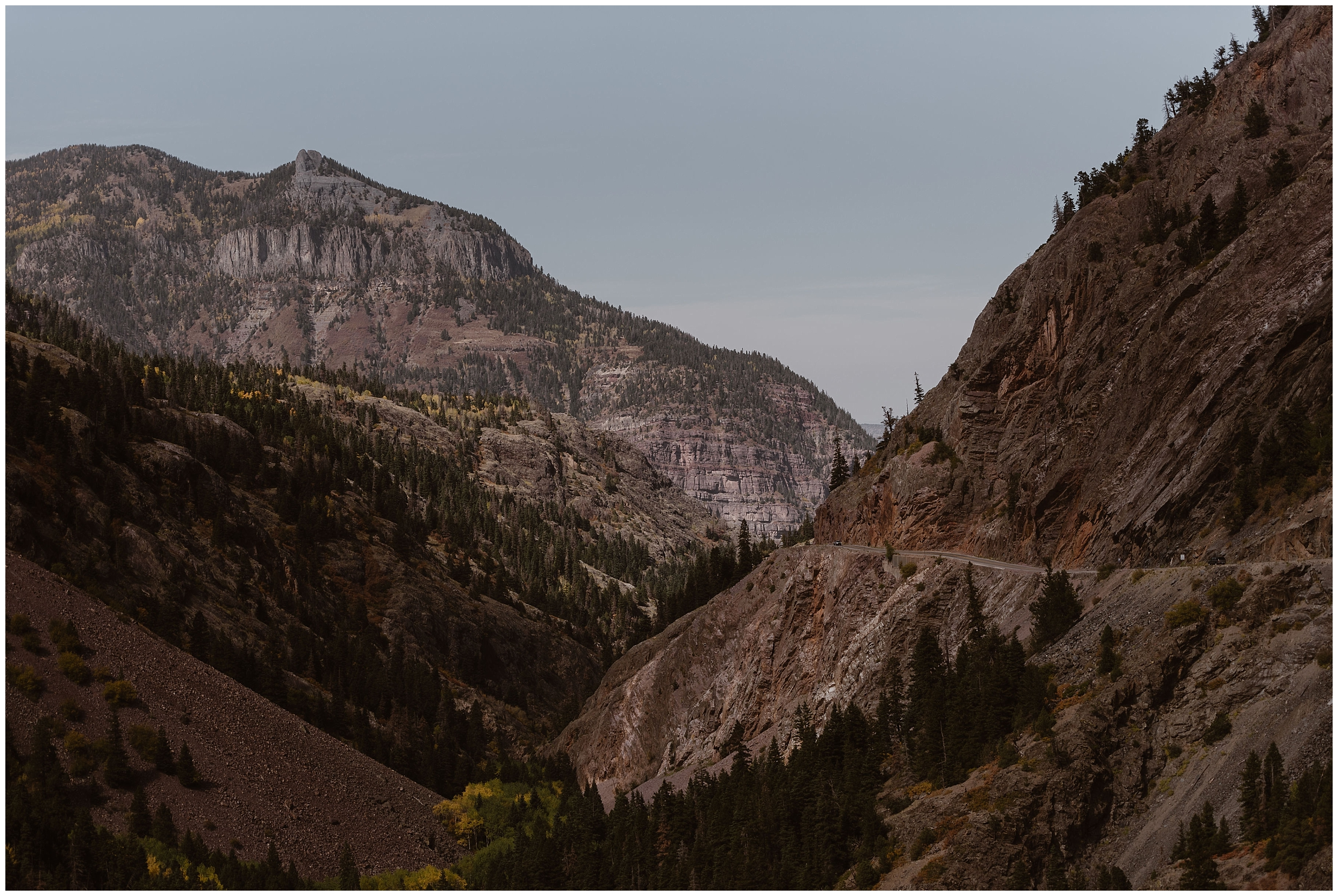In this elopement photo captured by Adventure Instead, an elopement photographer, the rocky red mountains of Ouray, Colorado are seen. A road is carved into the side of the mountain, a perfect place for a 4x4 wedding.