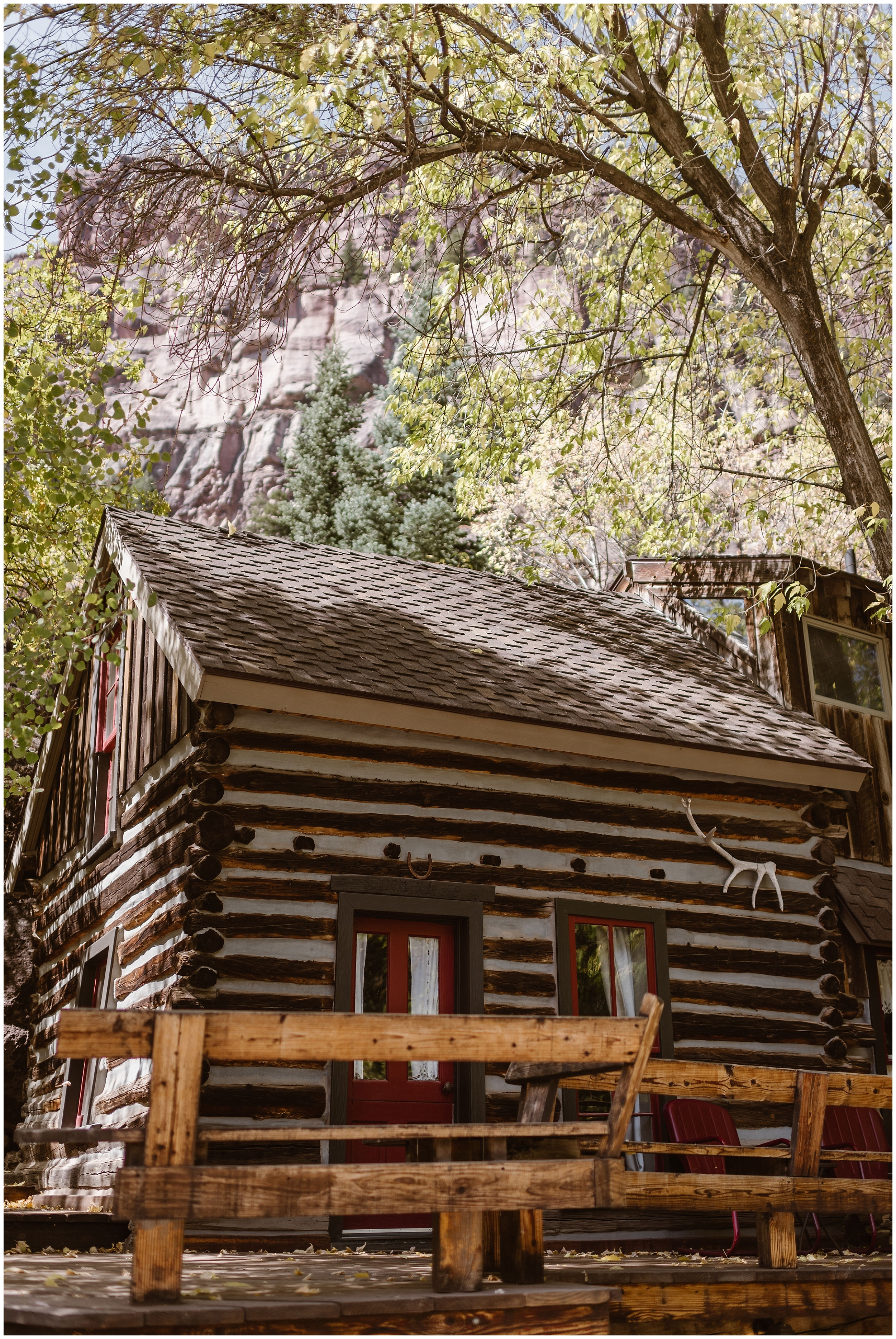 A tiny, crooked cabin is shown in this image captured by elopement wedding photographer Adventure Instead. The cabin, shaded by beautiful trees, is painted white and brown and has a quirky red door. In the background, rocky mountains peek through the trees.