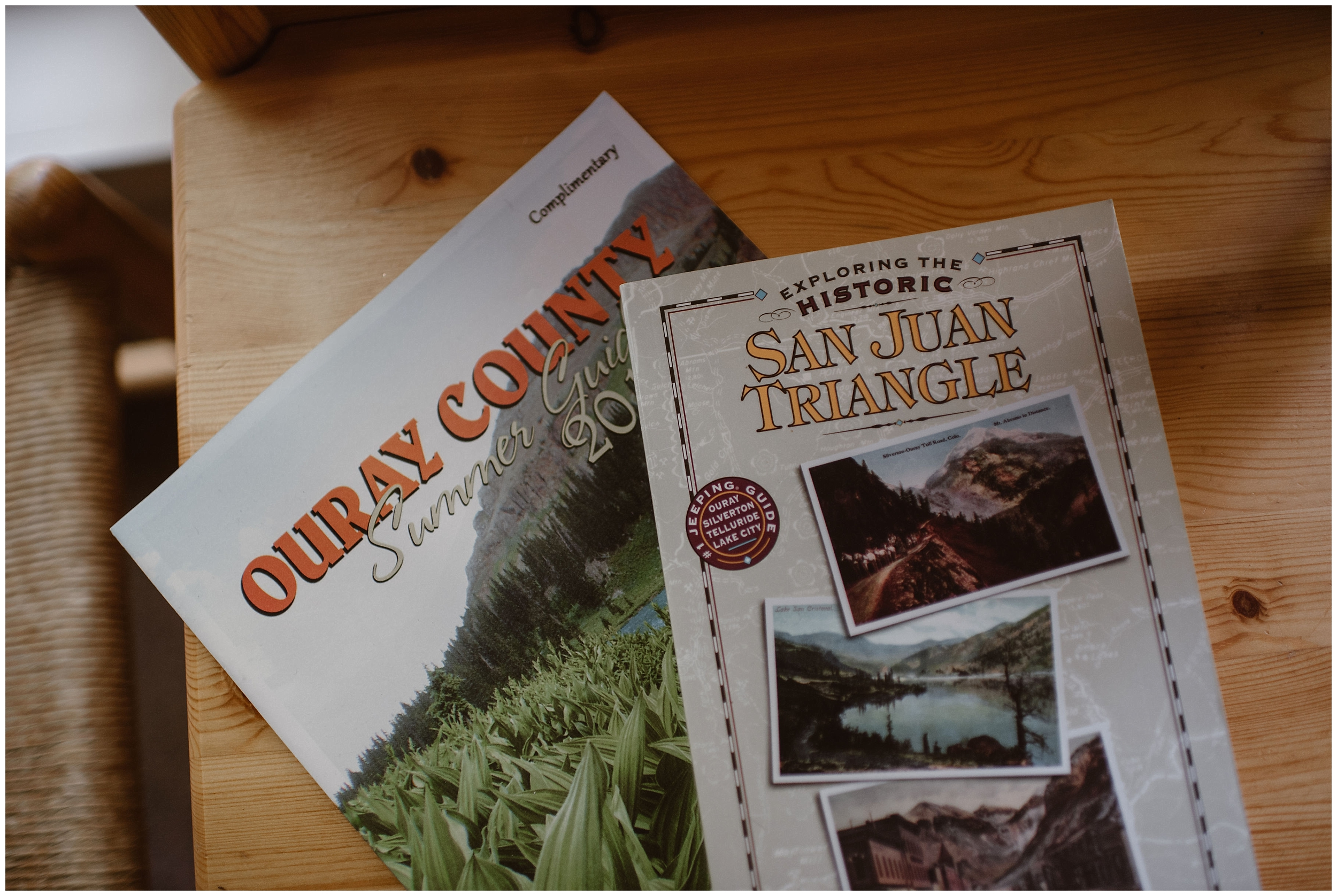 On a light-wood table lays a pamphlet for Ouray County and for exploring the San Juan Triangle. These items were found in a rented VRBO cabin (that was charming and crooked) that Ernie and Brian, the couple getting married, chose for their Colorado mountain wedding.