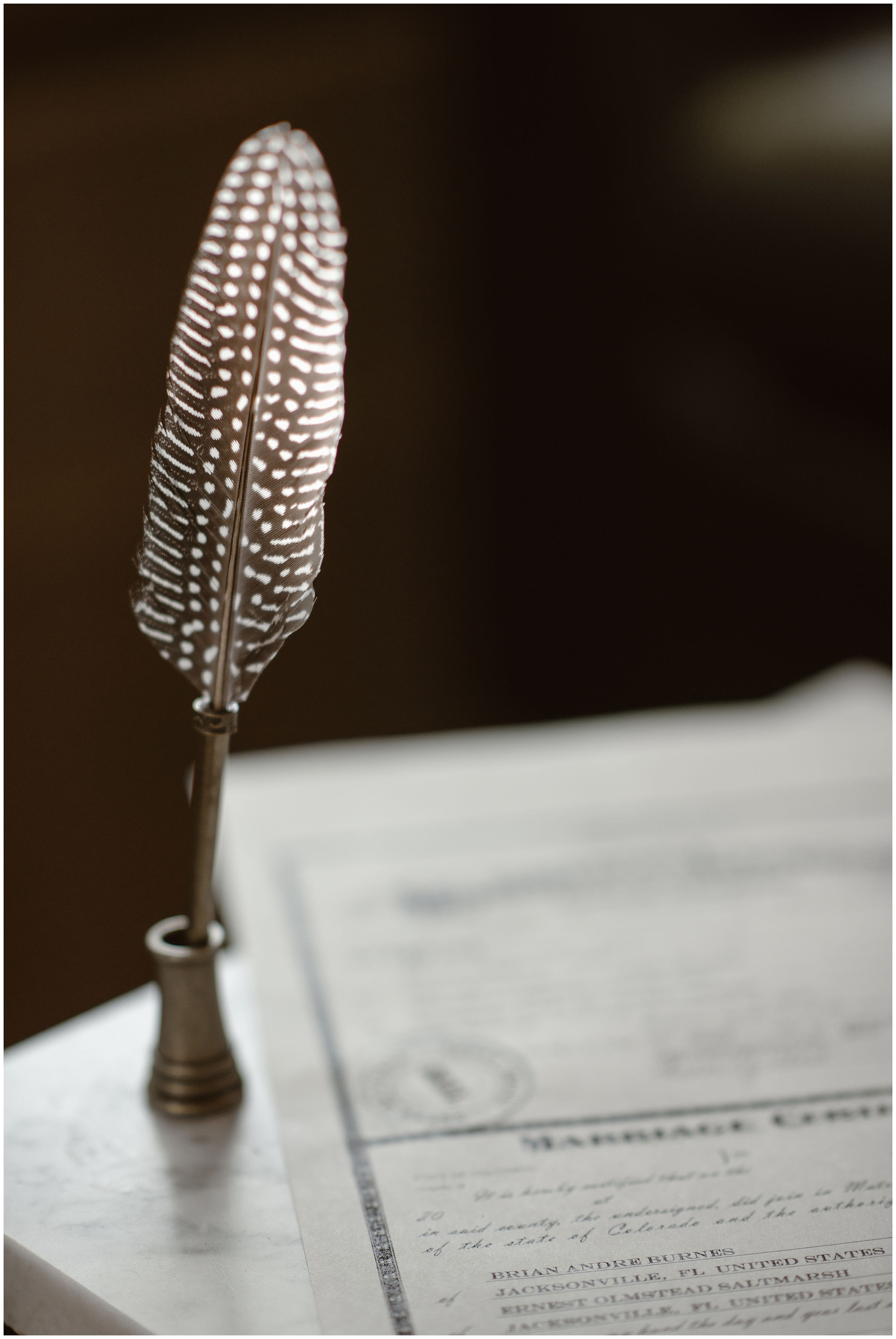 An old-fashioned quill pen stands on a marble counter top next to the faint image of a marriage license. Brian and Ernie, the couple getting married, chose to sign their marriage license during their elopement ceremony of their Colorado mountain wedding.