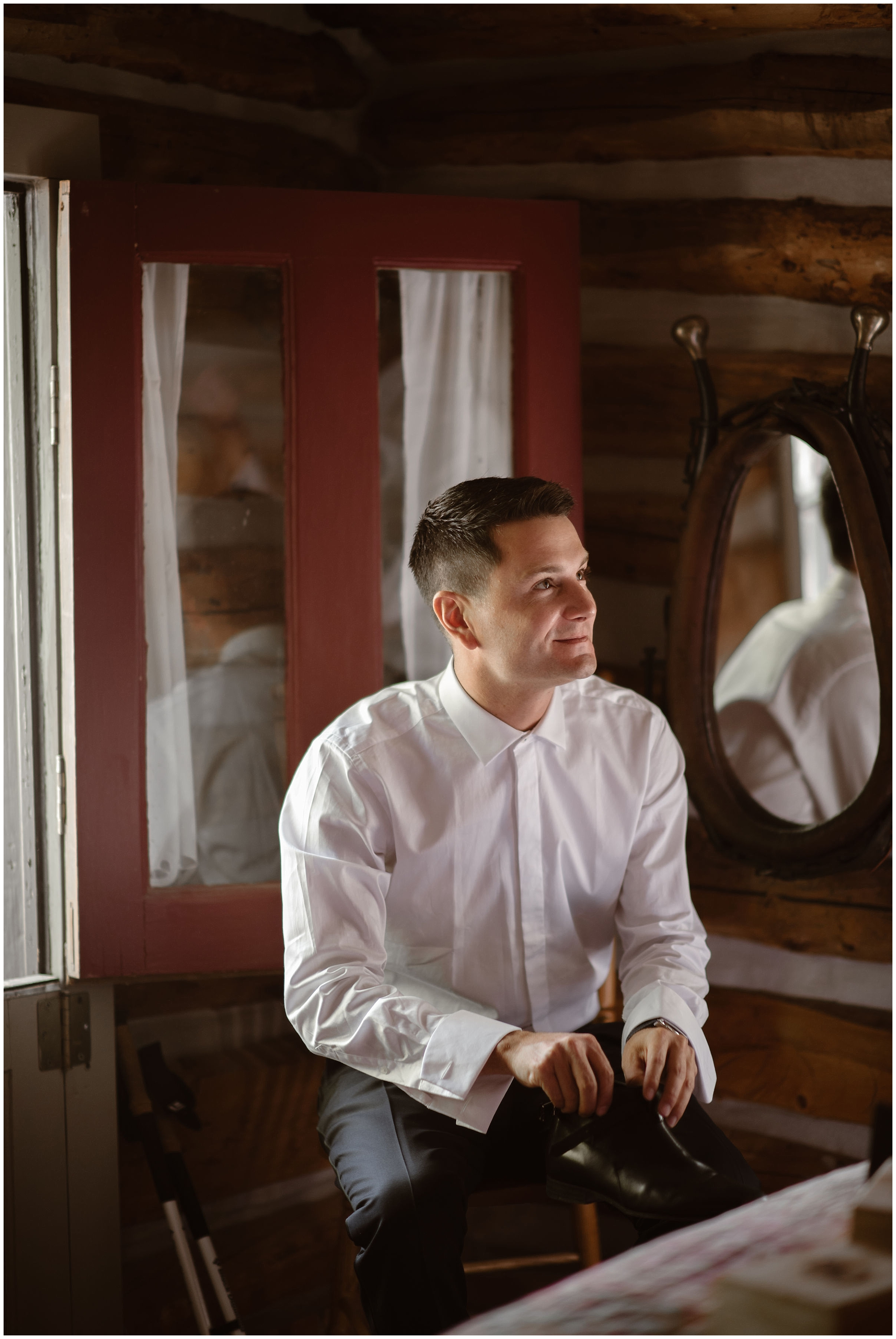 One of the grooms looks into the distance at his soon-to-be husband inside their rented VRBO cabin. He smiles as he holds his dress shoe in his hand while getting ready for their Colorado destination wedding.