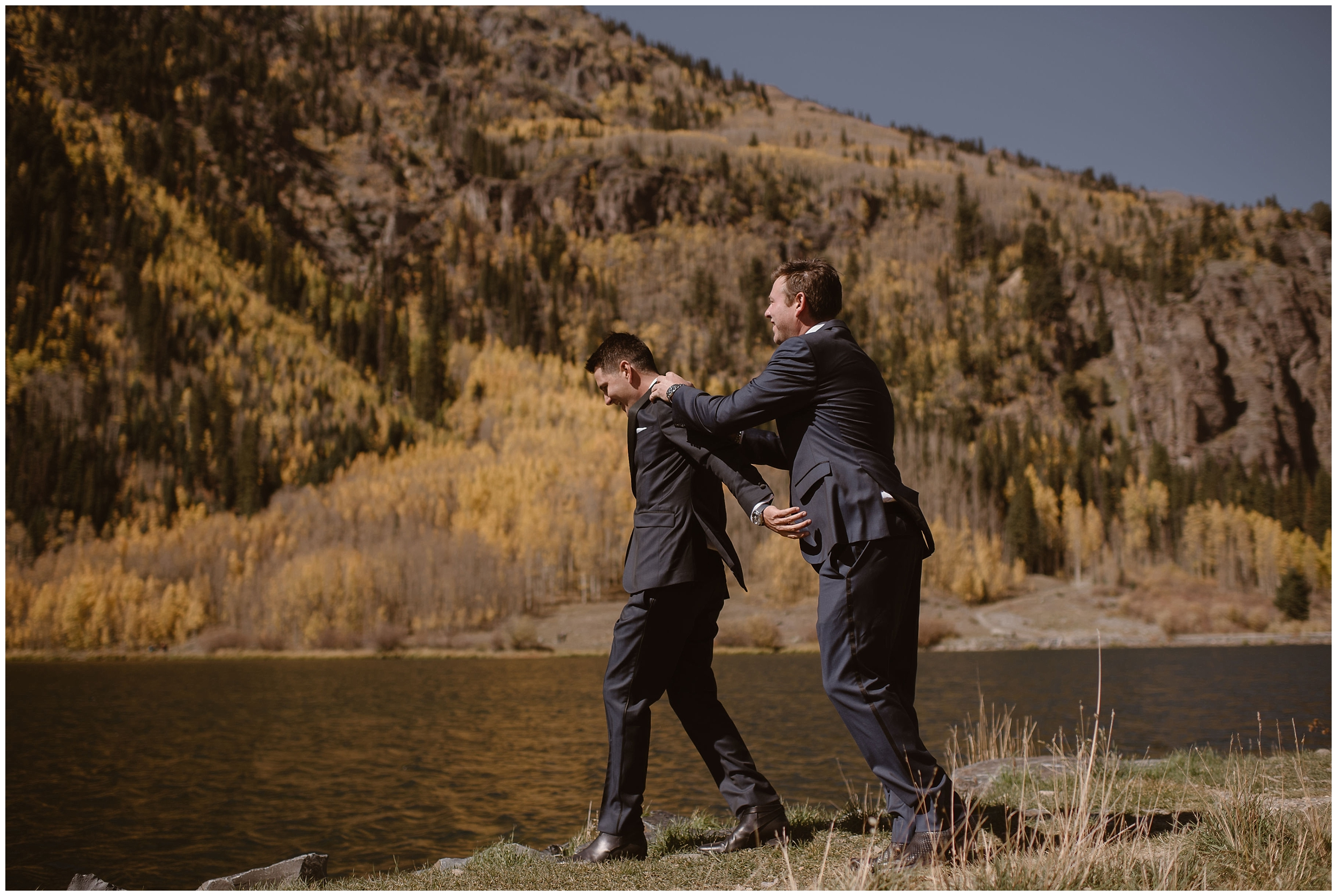 Brian and Ernie flirt and mess around next to a beautiful, sparkling alpine lake. The two grooms, fully dressed in their suits for their elopement ceremony, pose for elopement photos captured by Adventure Instead, an elopement wedding photographer.