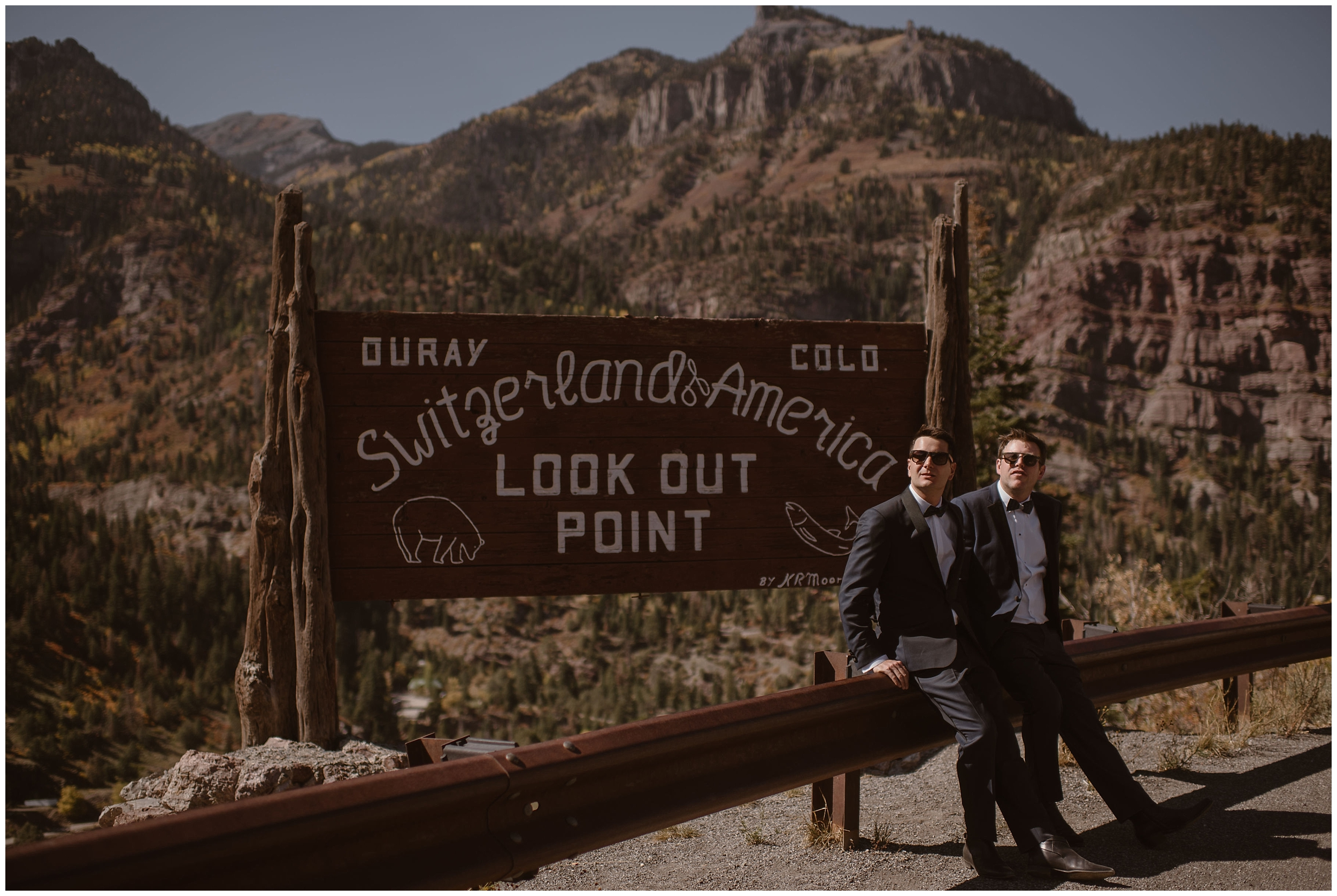 "The two grooms, Brian and Ernie, stand in front of a mountain range and a sign that states ""Ouray, Colorado. Switzerland of America."" The two of them wear their suits for their elopement ceremony and have dark black sunglasses on."