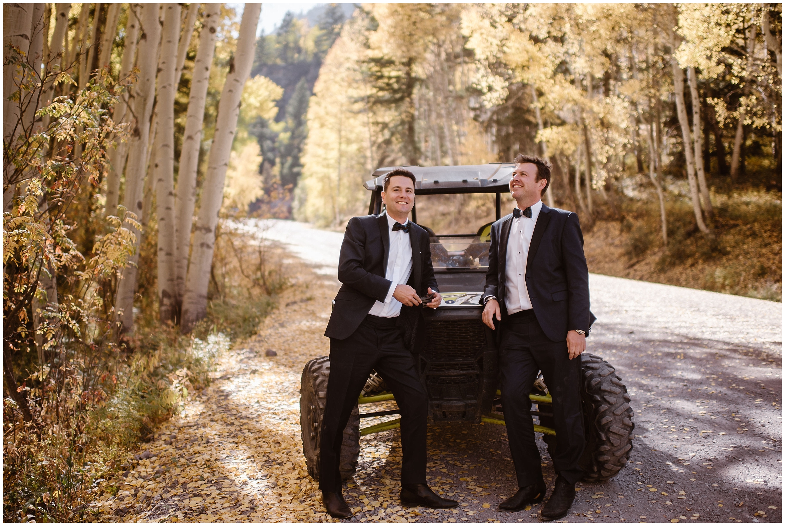 Brian and Ernie, the two grooms, pose in front of their off-road vehicle. The two lean against the side-by-side in their dark suits, fully prepared for their elopement ceremony. The gold and white aspen trees stand out vibrantly all around them.