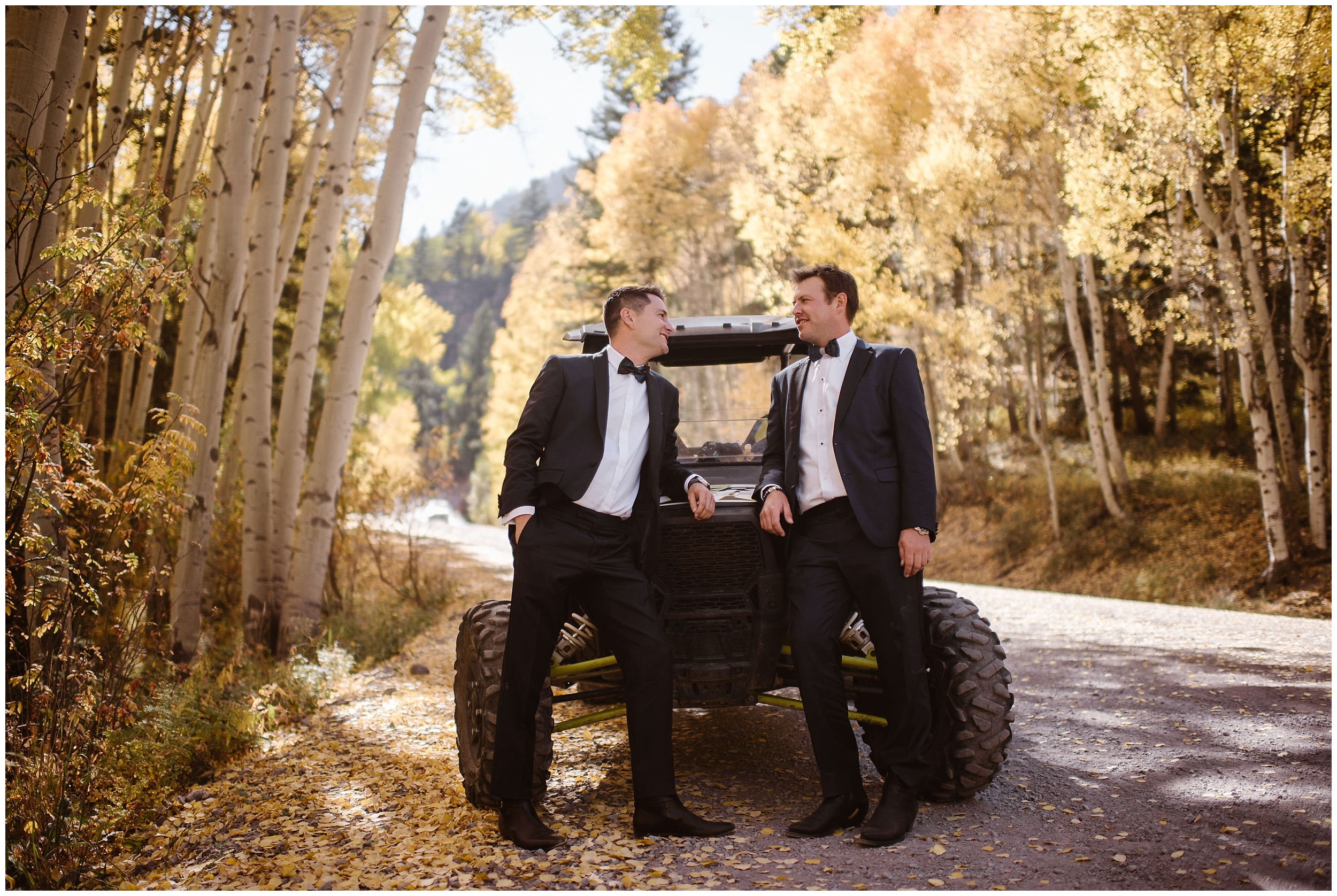 The two grooms, Brian and Ernie, lean up against their off-road vehicle that they parked in the middle of a beautiful, golden aspen grove. The two grooms are dressed in their suits and ready for their elopement ceremony, which they'll take the off-road vehicles to get to for their 4x4 wedding.
