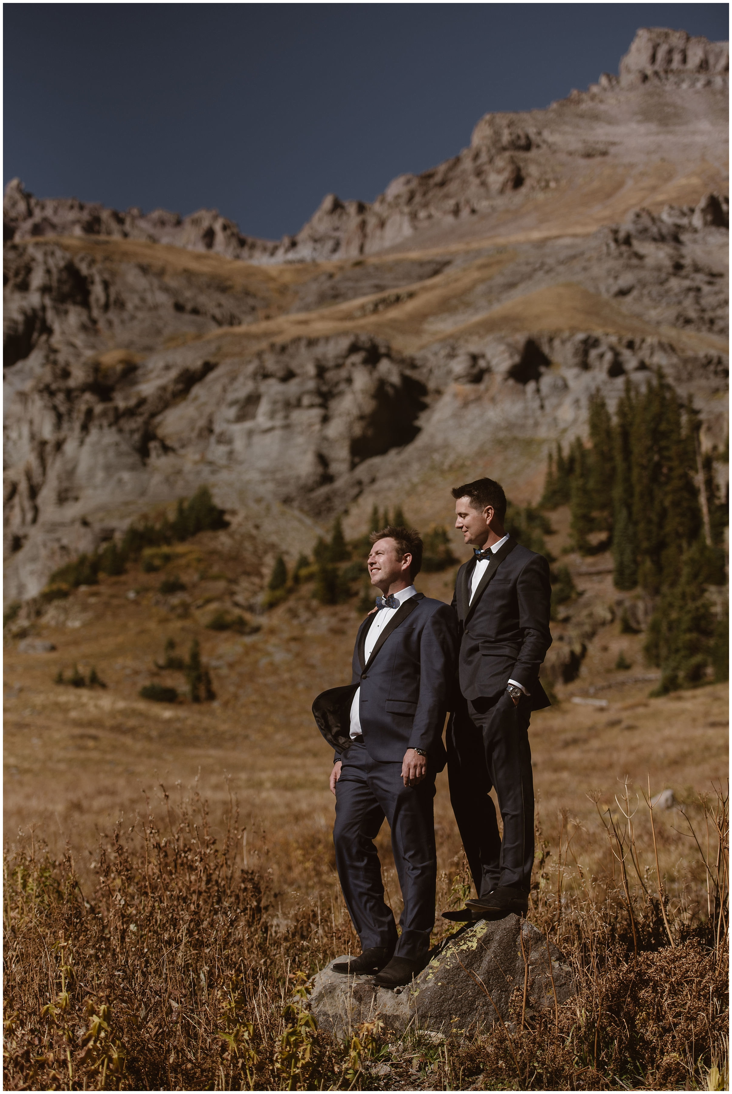 The two grooms, Brian and Ernie, stand up on a rock in the middle of a golden field. Behind them, an enormous, rocky mountain dotted in vibrant green and gold trees can be seen. These elopement photos were captured by Colorado elopement photographer Adventure Instead.