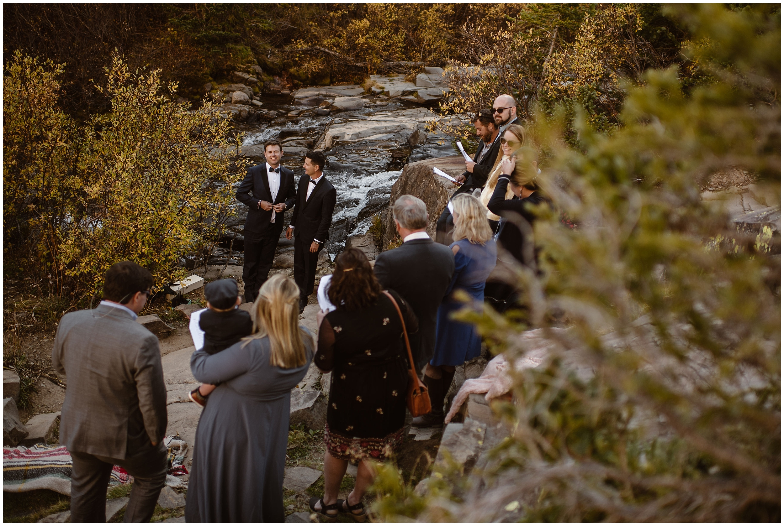 Brian and Ernie stand next to a rushing river during their elopement ceremony as their immediate family gathers around them for their Colorado mountain wedding. Everyone is holding a special document with detailed blurbs for their parts of their ceremony.