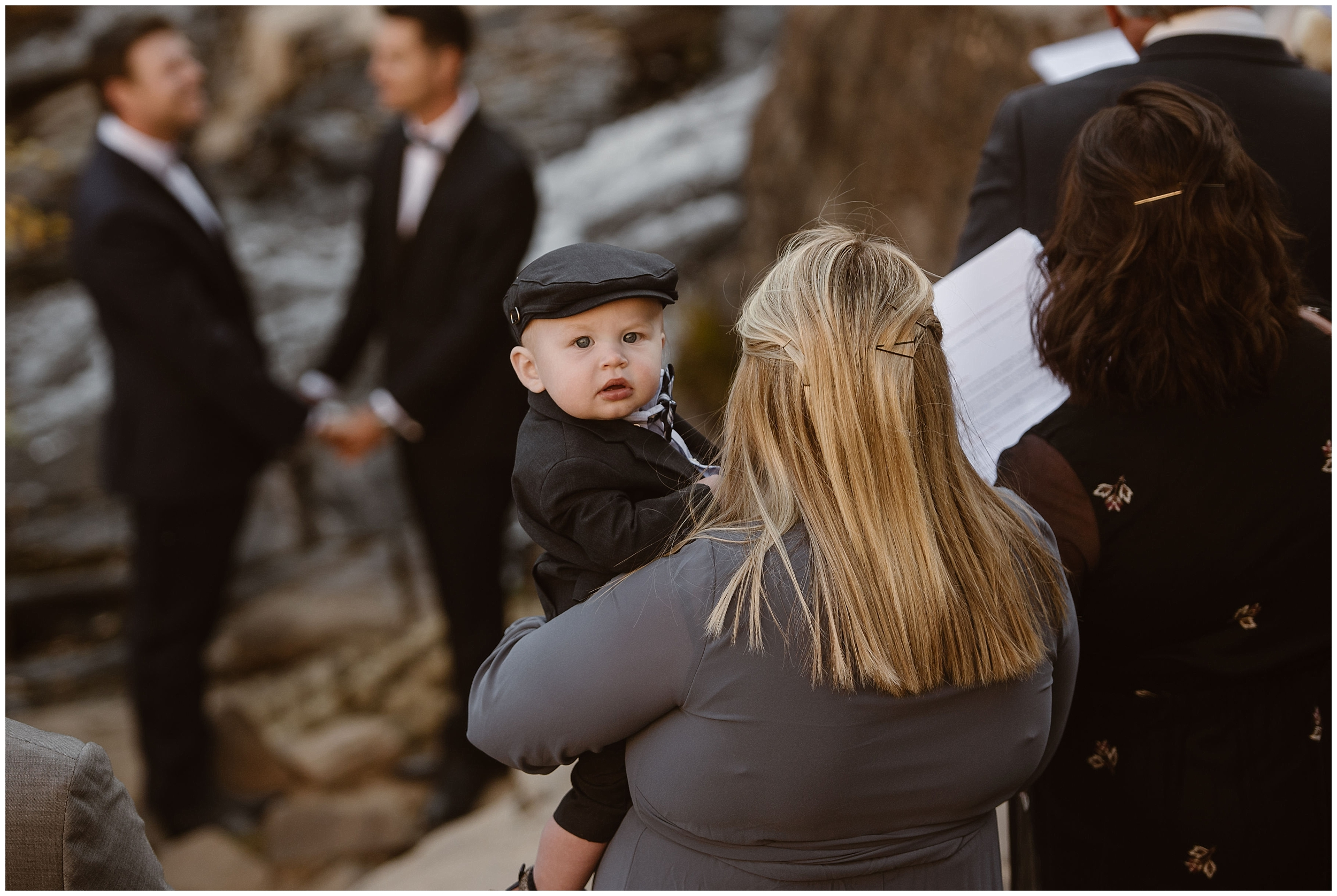 The tiniest guest at Brian and Ernie's elopement peeks up over his mother's shoulder. Their 9-month-old godson , wearing a pageboy hat, looks into the camera held by Adventure Instead, an elopement wedding photographer who captured Brian and Ernie's Colorado mountain wedding.