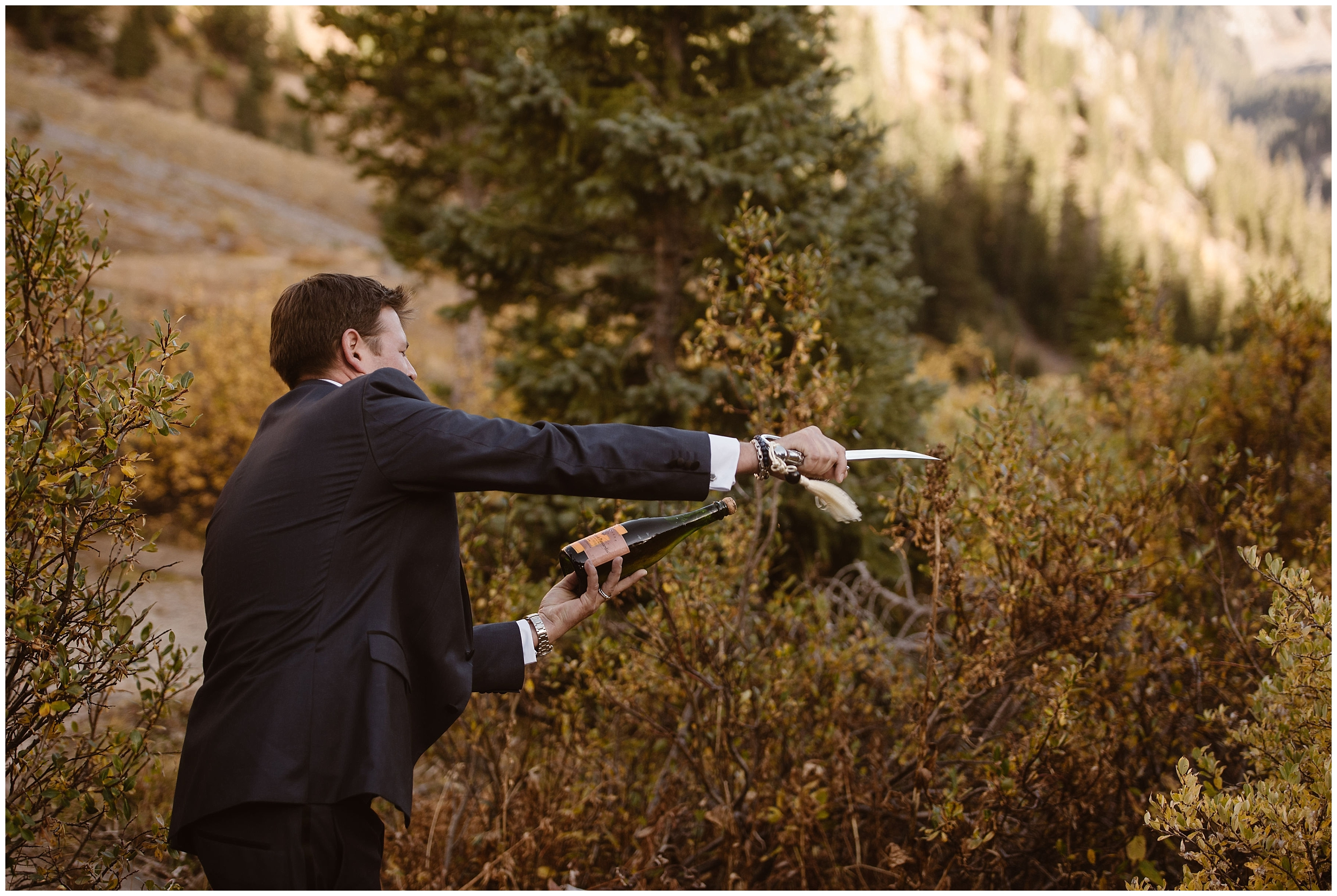 One of the grooms reaches out with his Samurai sword to cut the champagne cork clear off the bottle of champagne for their reception after eloping.