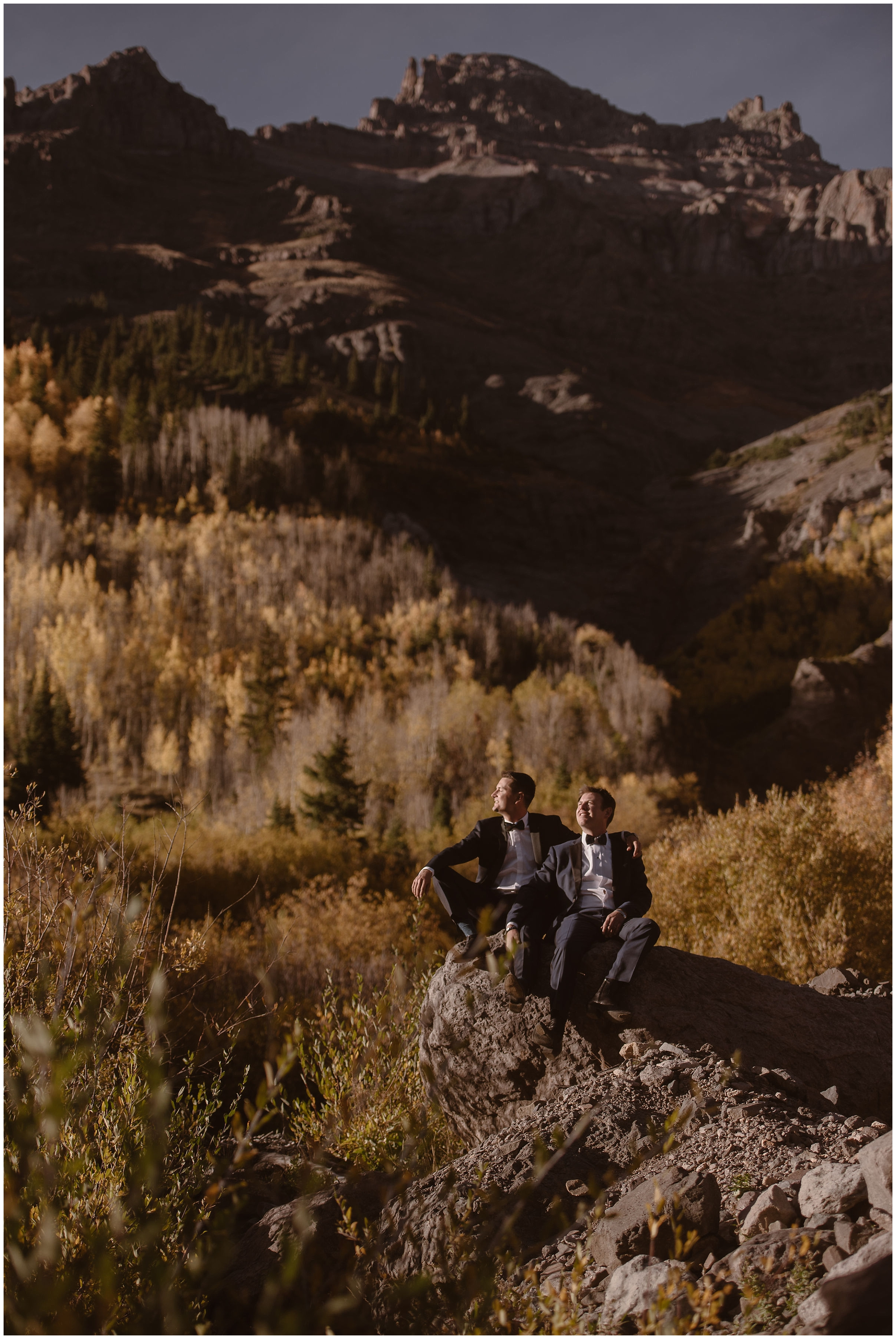 Brian and Ernie, just married, sit on a jagged, rock platform as the sun sets and casts them in a shadow. All around them, golden hues are painted into the wildflowers, the trees, the grass. Brian and Ernie chose this destination elopement location so their elopement photos would show the golden hues of Fall.