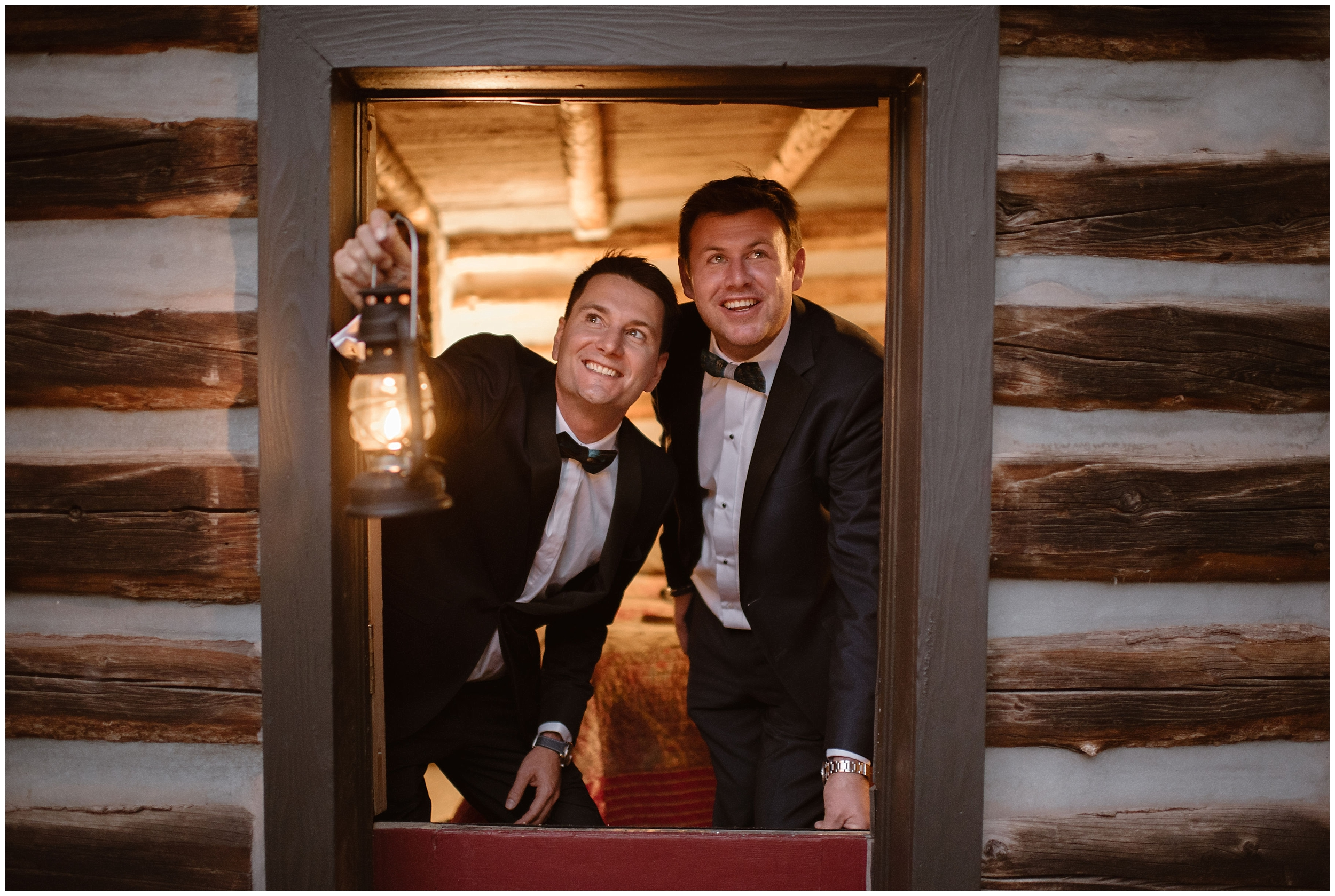 Brian and Ernie lean out of their VRBO cabin door holding a lantern, their faces illuminated as the setting sun closes in on their perfect Colorado mountain wedding.