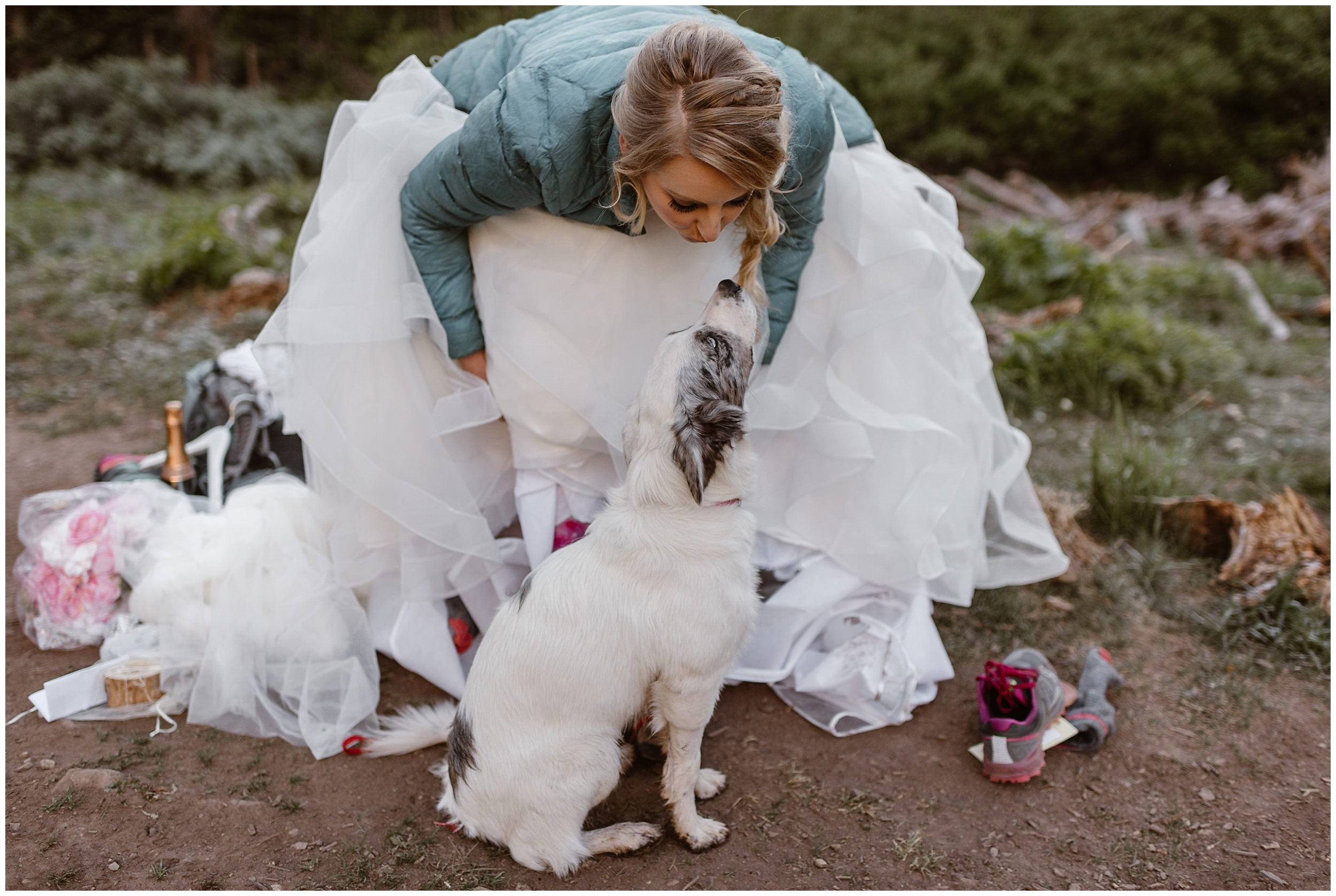 A bride an dog are featured in this elopement photo captured by Adventure Instead, an elopement photographer. The bride leans down over her fluffy dress to make a kissing face at her white and grey pup.