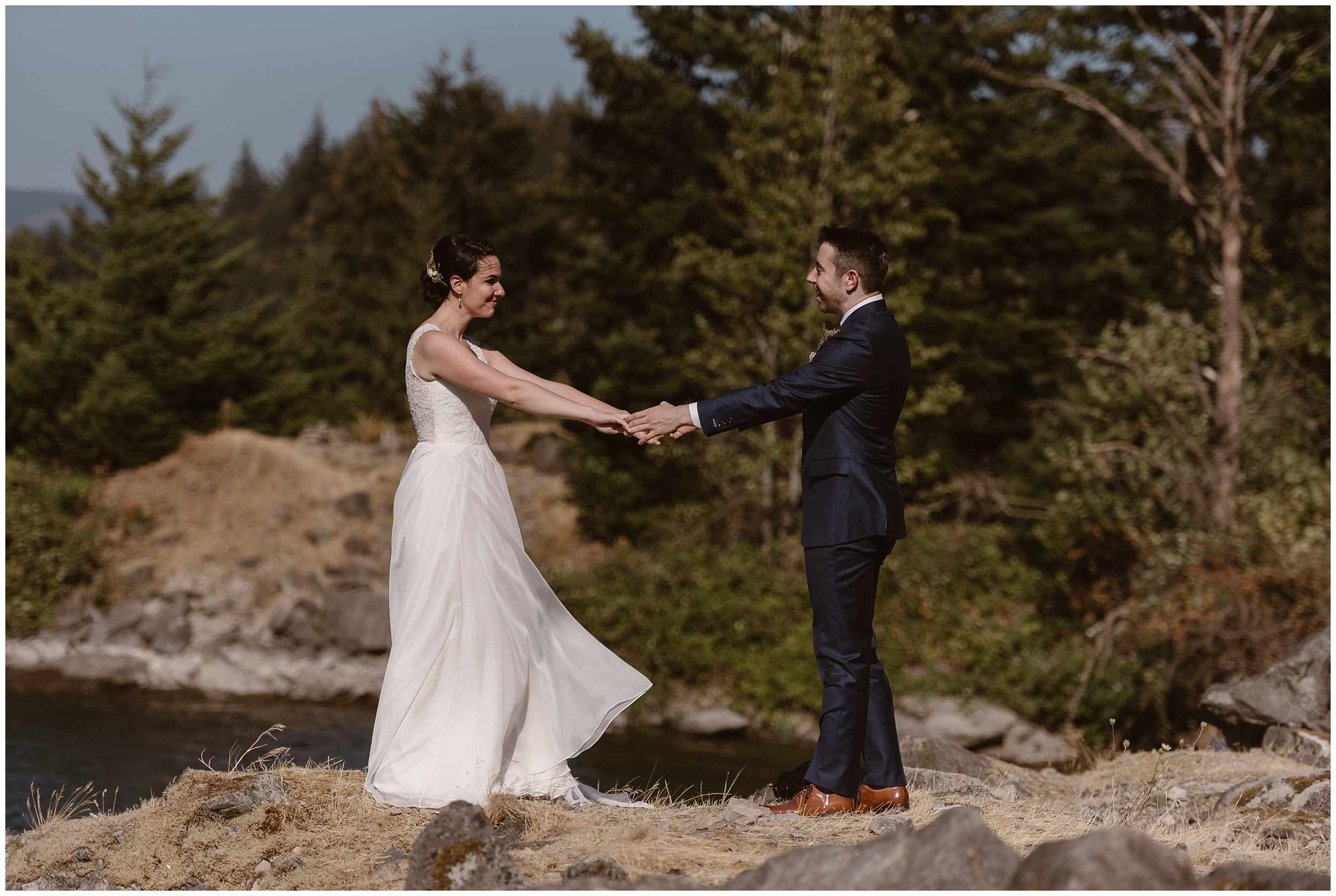 The bride and groom take hands as they gaze at each other during their first look before their elopement ceremony. As they stand on the edge of a cliff on the Columbia River Gorge, they take a moment to absorb the dreamy, moody PNW feels before their Oergon elopement.
