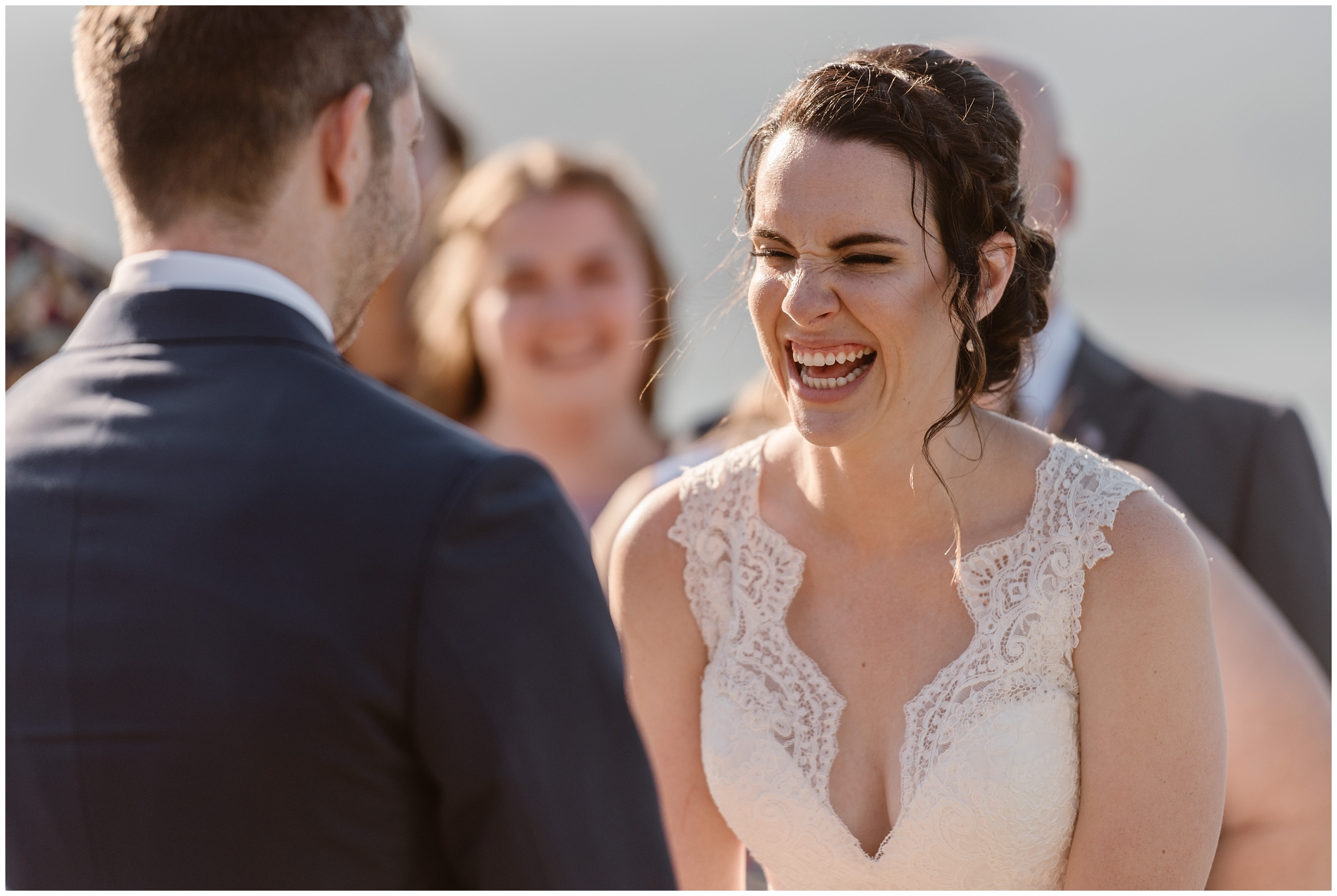 Lauryn leans in close to David to laugh during their Columbia River Gorge wedding. Behind her, members of her family laugh along with her during their elopement ceremony.