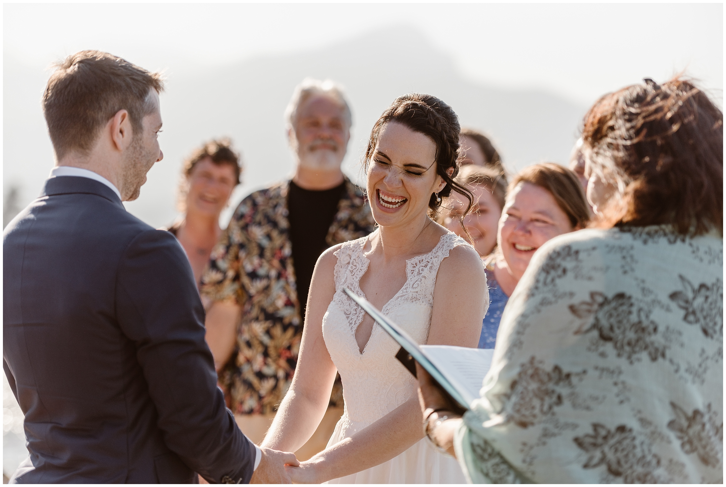 Lauryn and David hold hands during their Columbia River Gorge wedding. Lauryn, closing her eyes as the officiant marries them, laughs out loud at David. Behind, them, their family looks on during their Oregon elopement.