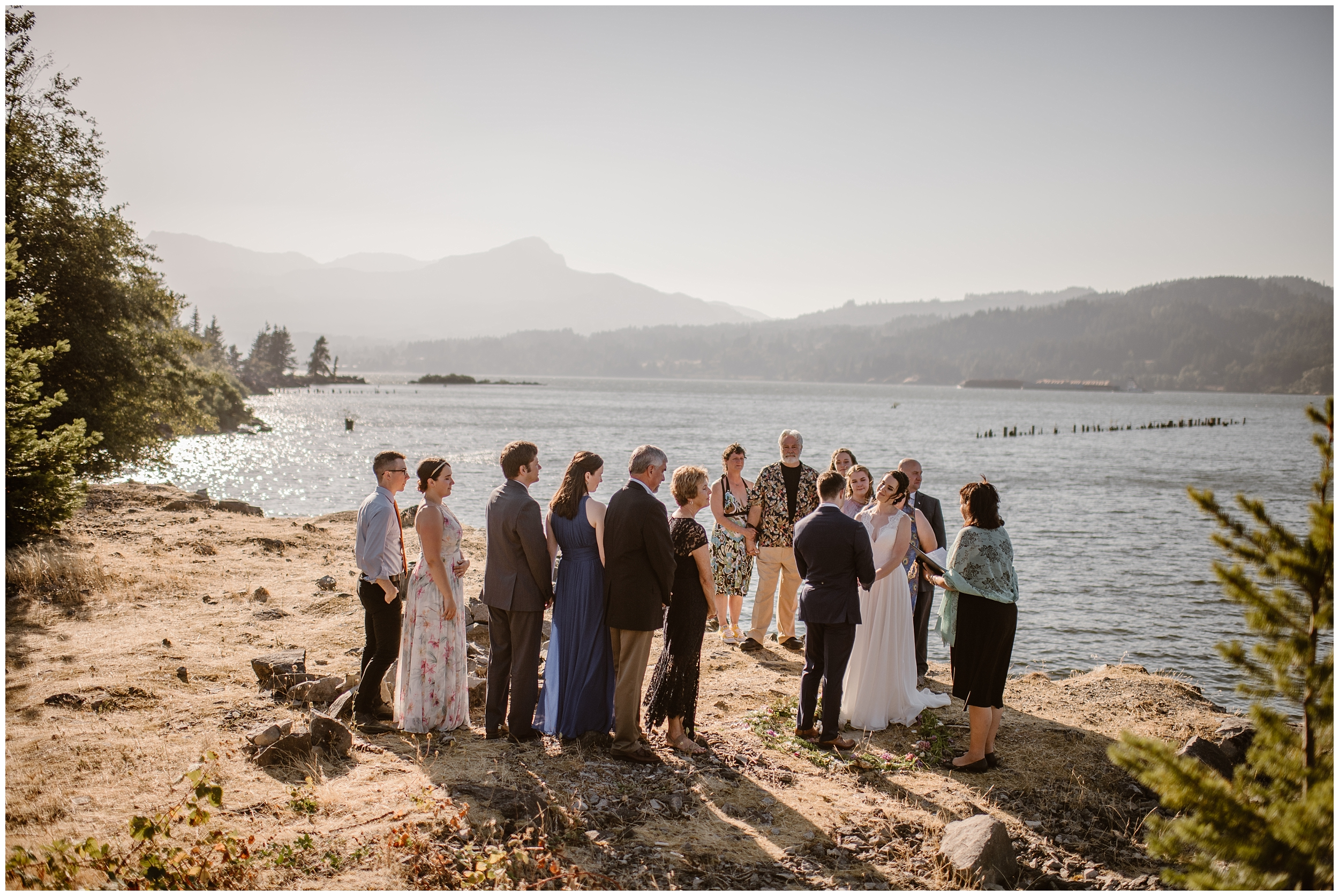 In these Oregon elopement photos, Lauryn and David's entire family is captured as they all stand on the banks of the Columbia River watching the elopement ceremony. In the background, mountain peaks and dark green trees can be seen.