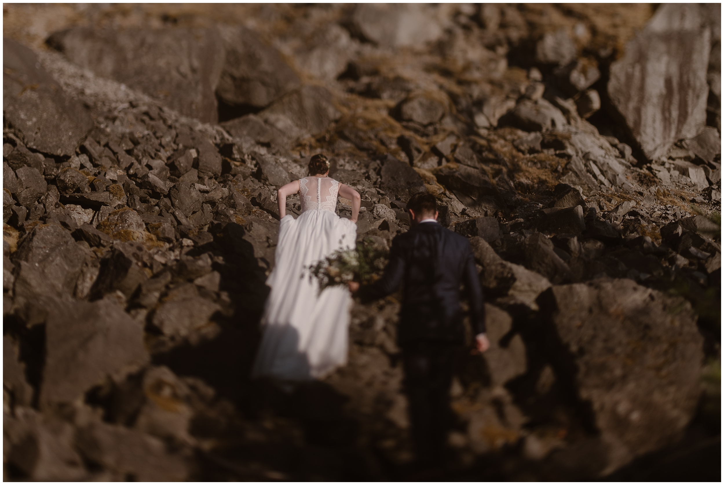Lauryn and David climb up the rocky side of the Columbia River Gorge, still in their wedding attire. Golden light and shadow casts upon them on the craggy rocks. David carries Lauryn's bouquet.