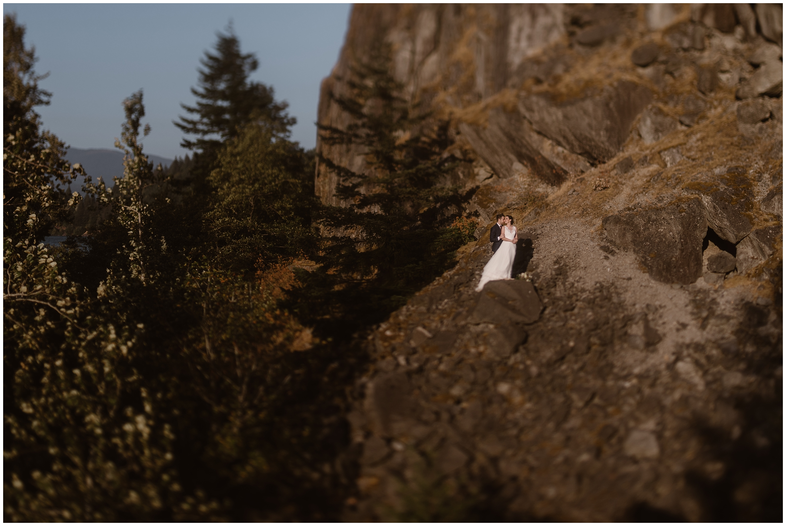 Lauryn and David embrace on the side of an enormous, golden rock in the Columbia River Gorge for some of their elopement photos. Exploring after their elopement ceremony was one of their best elopement ideas, especially for additional elopement photos.