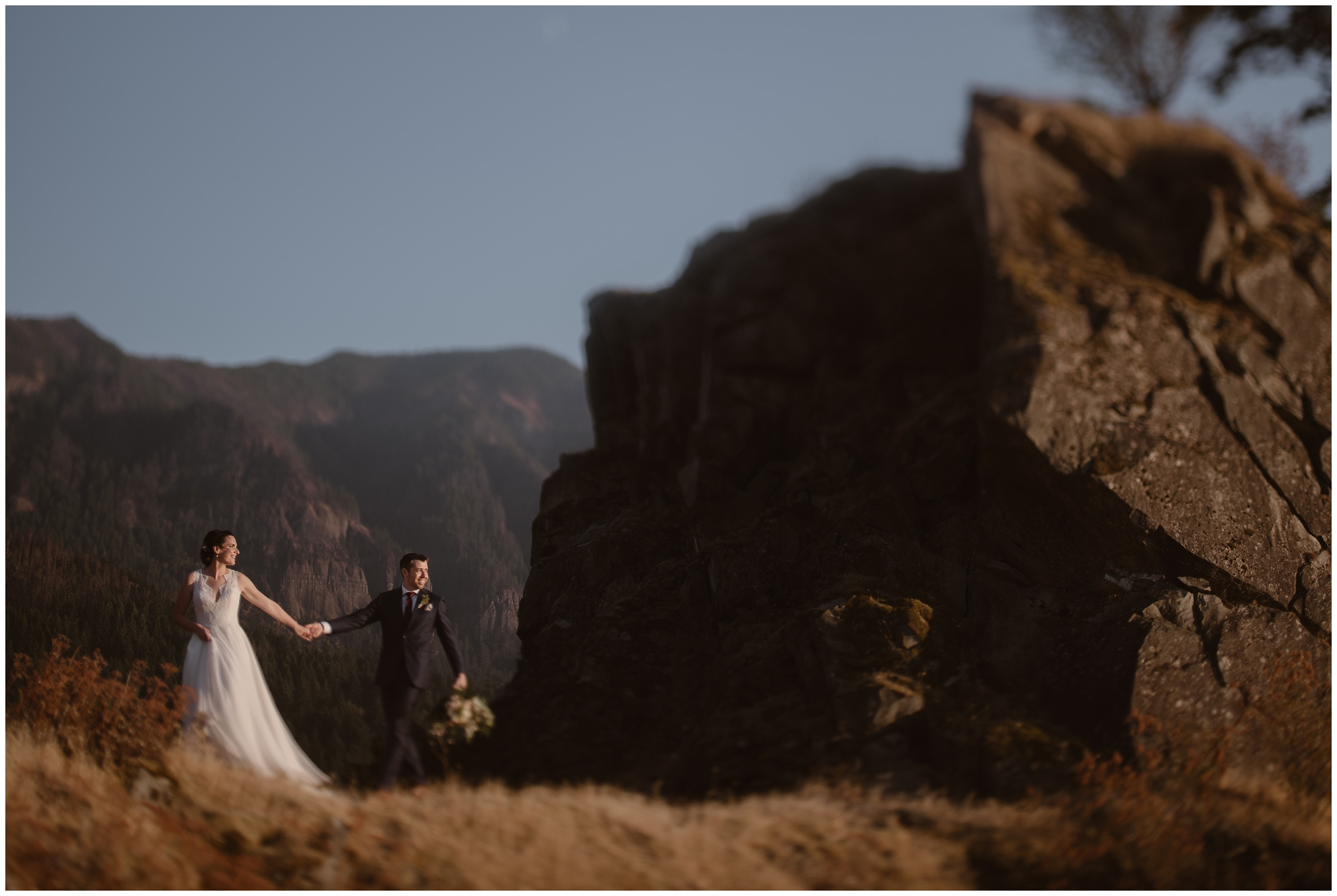 Lauryn, holding David's hand, leads him away from an enormous rock as they walk through a golden meadow. David, still holding Lauryn's bouquet, follows behind as he looks off into the distance at the Columbia River and the PNW islands dotting the river.