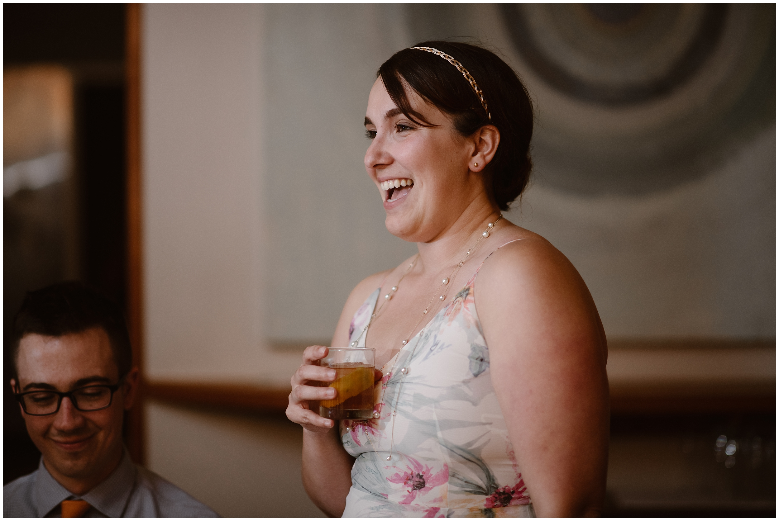 A family member stands up at the table during the party after eloping and gives a toast. The guest, smiling, holds a drink her hand as she stares at the bride and groom during their reception after elopement.