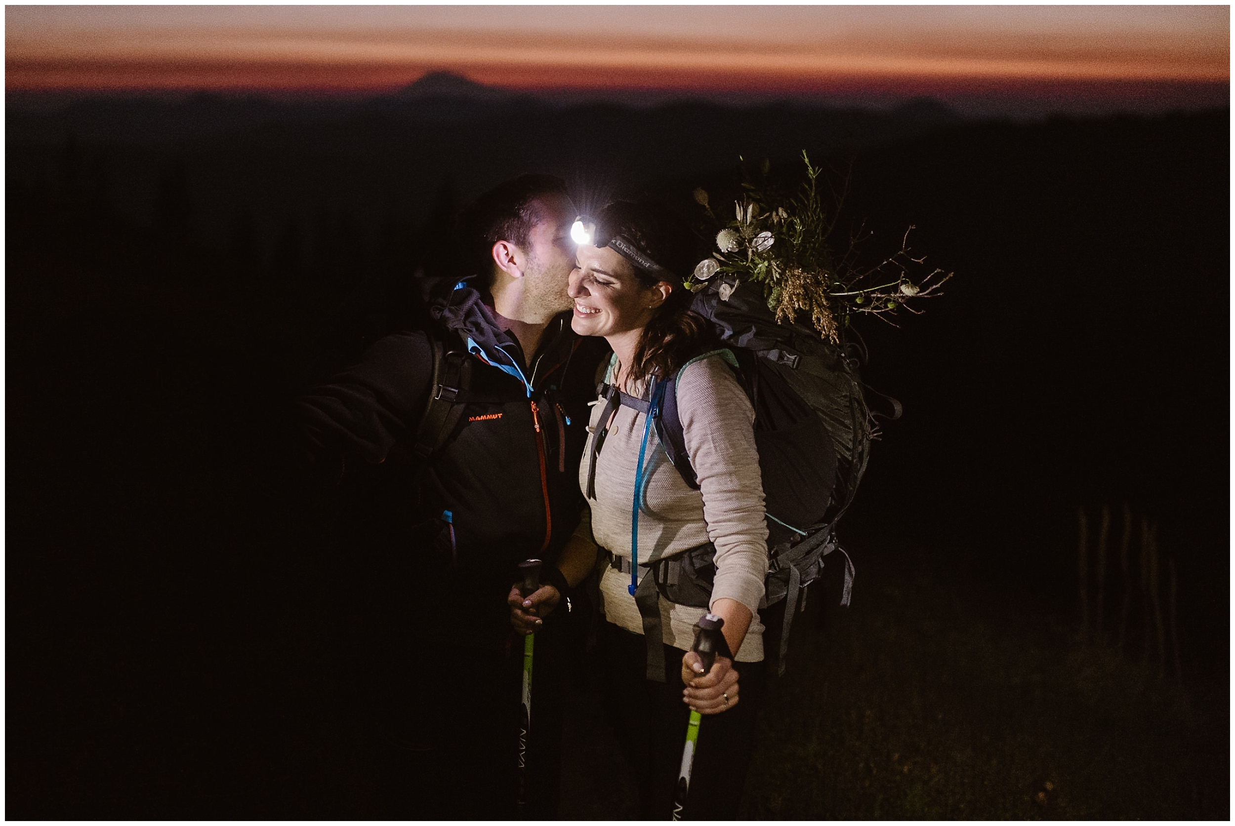 David leans in to kiss Lauryn on the cheek during their sunset hike. With just their headlamps to light their way, they'begin to hike up to elope in Washington State. The sun slowly rises behind them in the background.