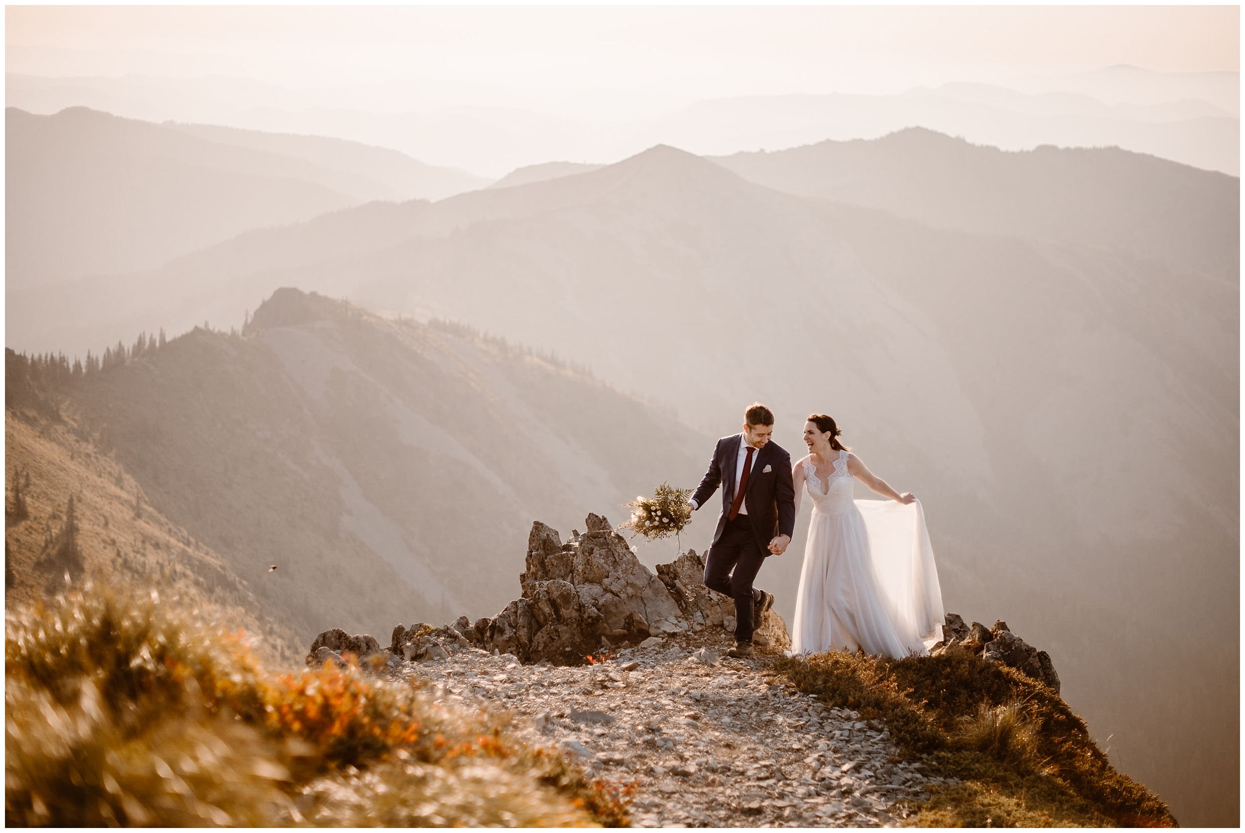 Lauryn and David hold hands as they stand at the edge of a the mountaintop during their sunrise elopement in Washington state. At the top of the mountain, there's a misty fog that surrounds Lauryn and David in their wedding clothes.