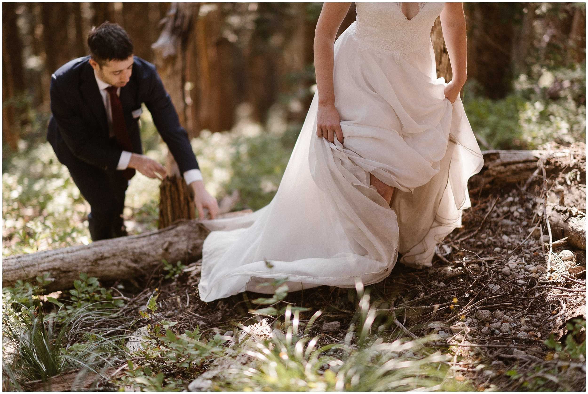 David reaches down to help Lauryn free her dress from a stump as they hike back down the mountain in their wedding attire. Hiking in their wedding outfits was one of the unique elopement ideas they wanted to capture in their elopement pictures.