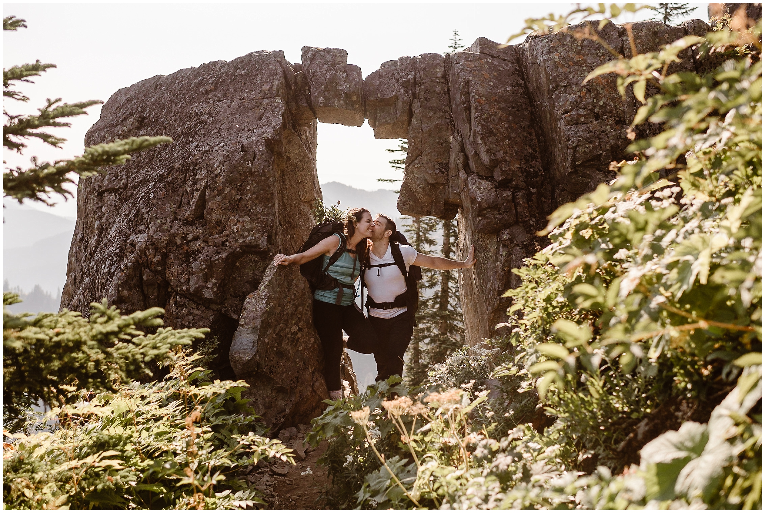 Lauryn and David pose beneath a rock formation during their Washington state elopement ceremony, During their hike down, they can finally see the trail they hiked up to elope in Washington state.
