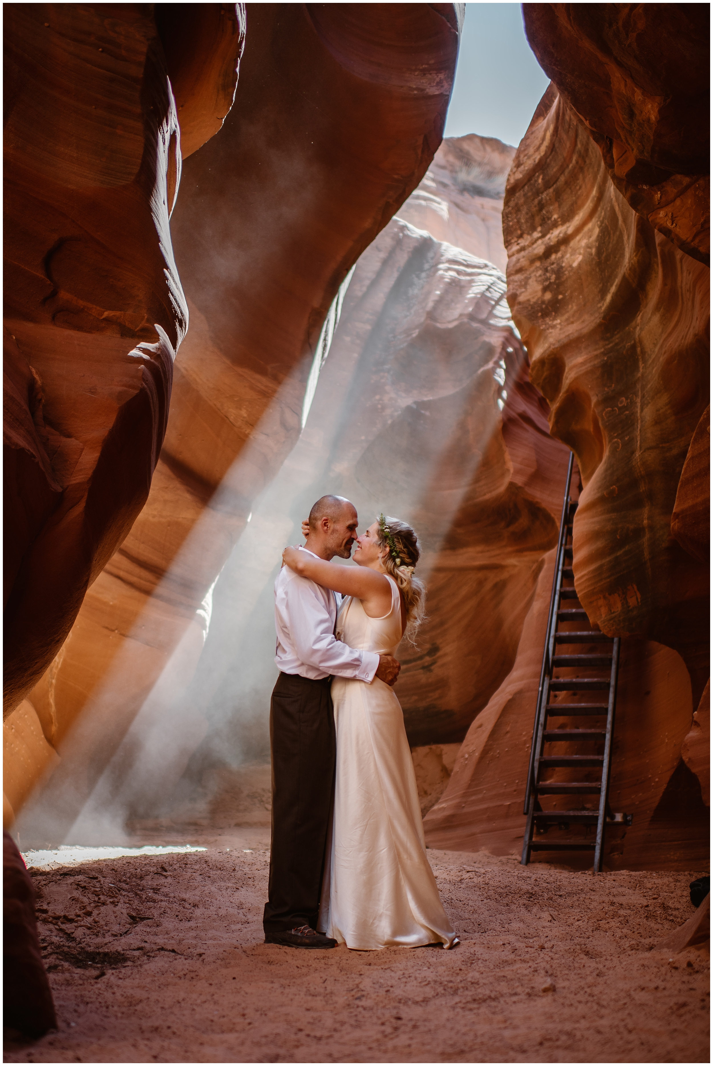 A bride and groom pull each other close in a red and orange slot canyon. In the background, a ladder can be seen leading down into the canyon, beautiful beams of light are hitting specific spots in the canyon. This is one of the most beautiful elopement locations in the world— but there are so many to choose from!
