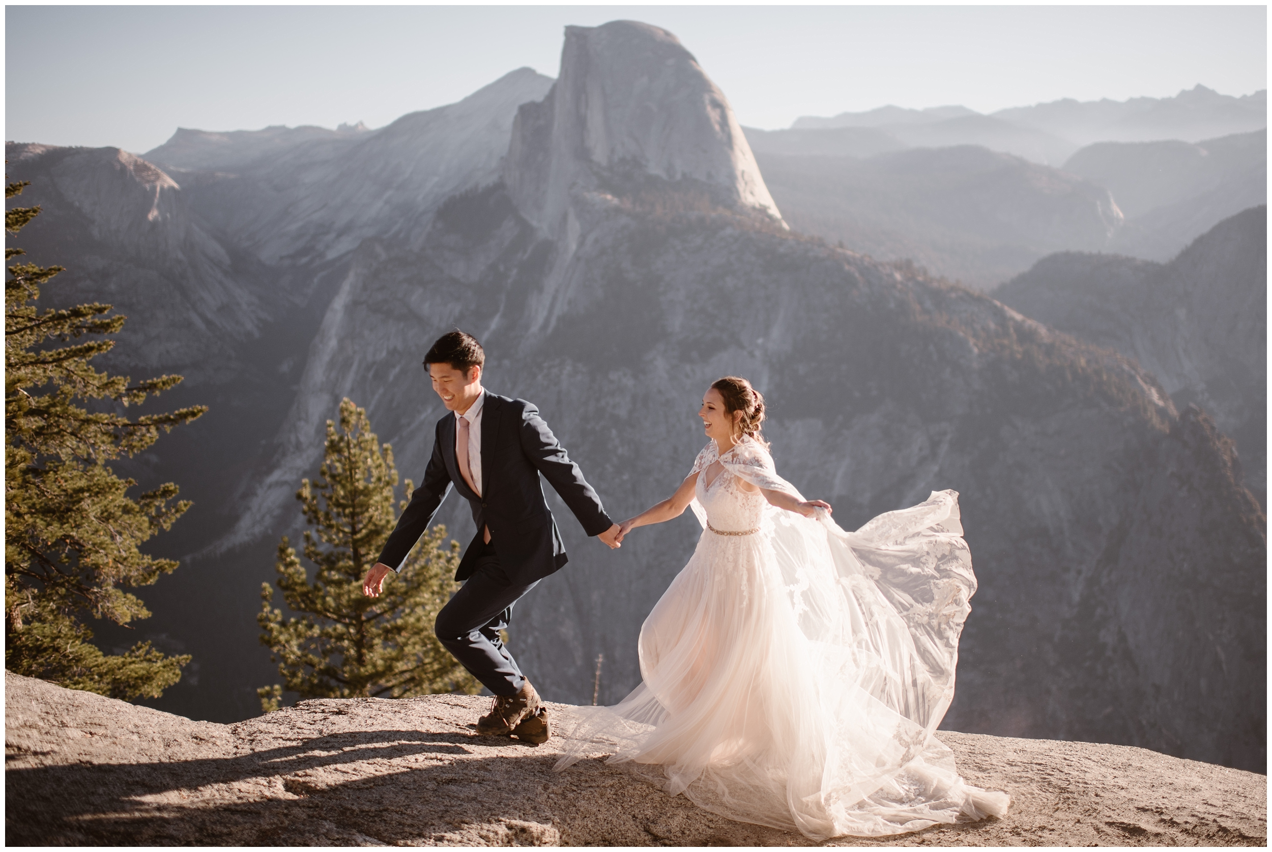 A bride and groom take hands and run on the side of a mountainous cliff in Yosemite National Park. A Yosemite National Park elopement was one of this couple's ideal small wedding ideas. That's one of the benefits of eloping—you can pick any location you want!